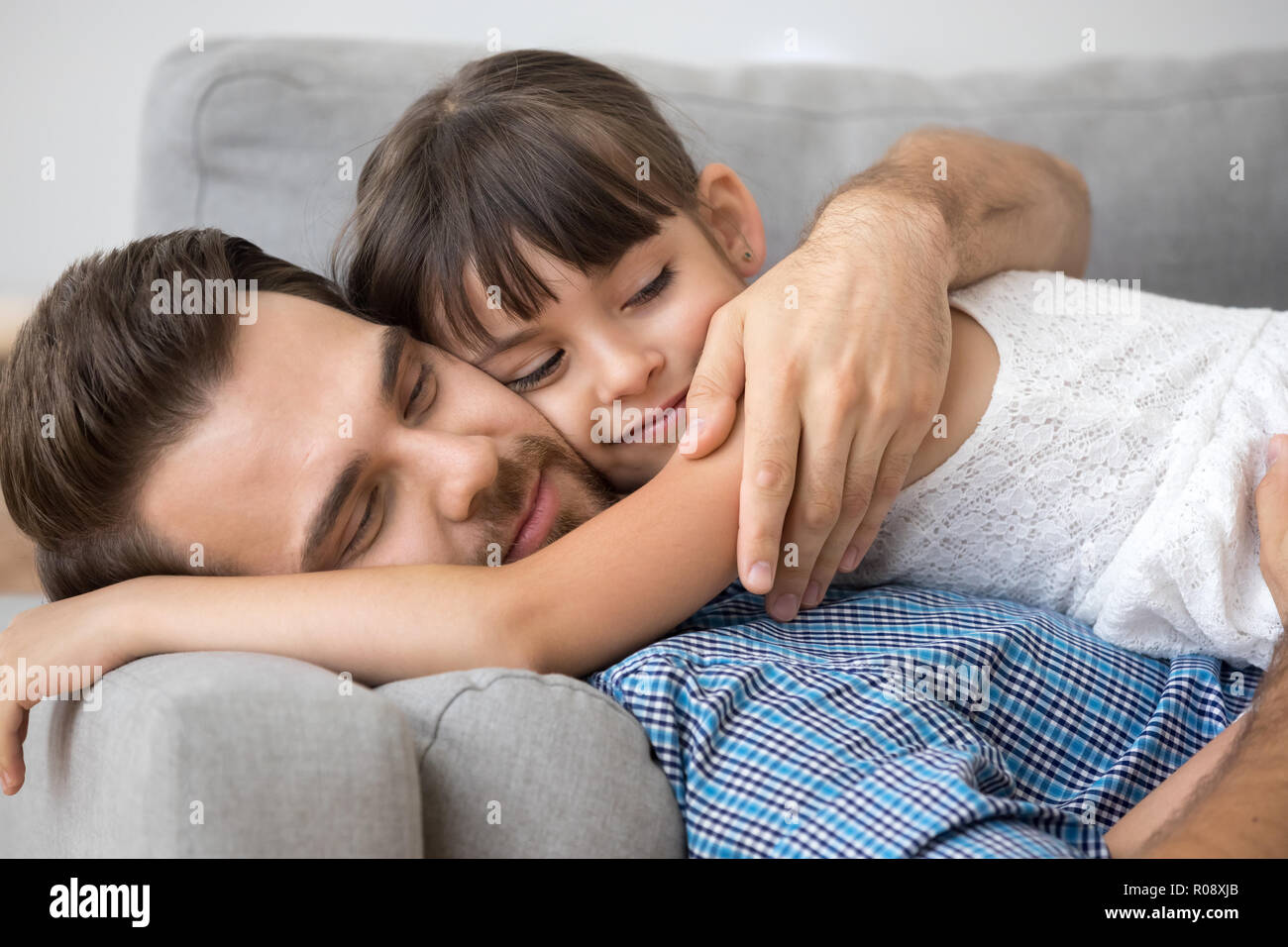 Father and daughter hugging lying on sofa - Stock Image