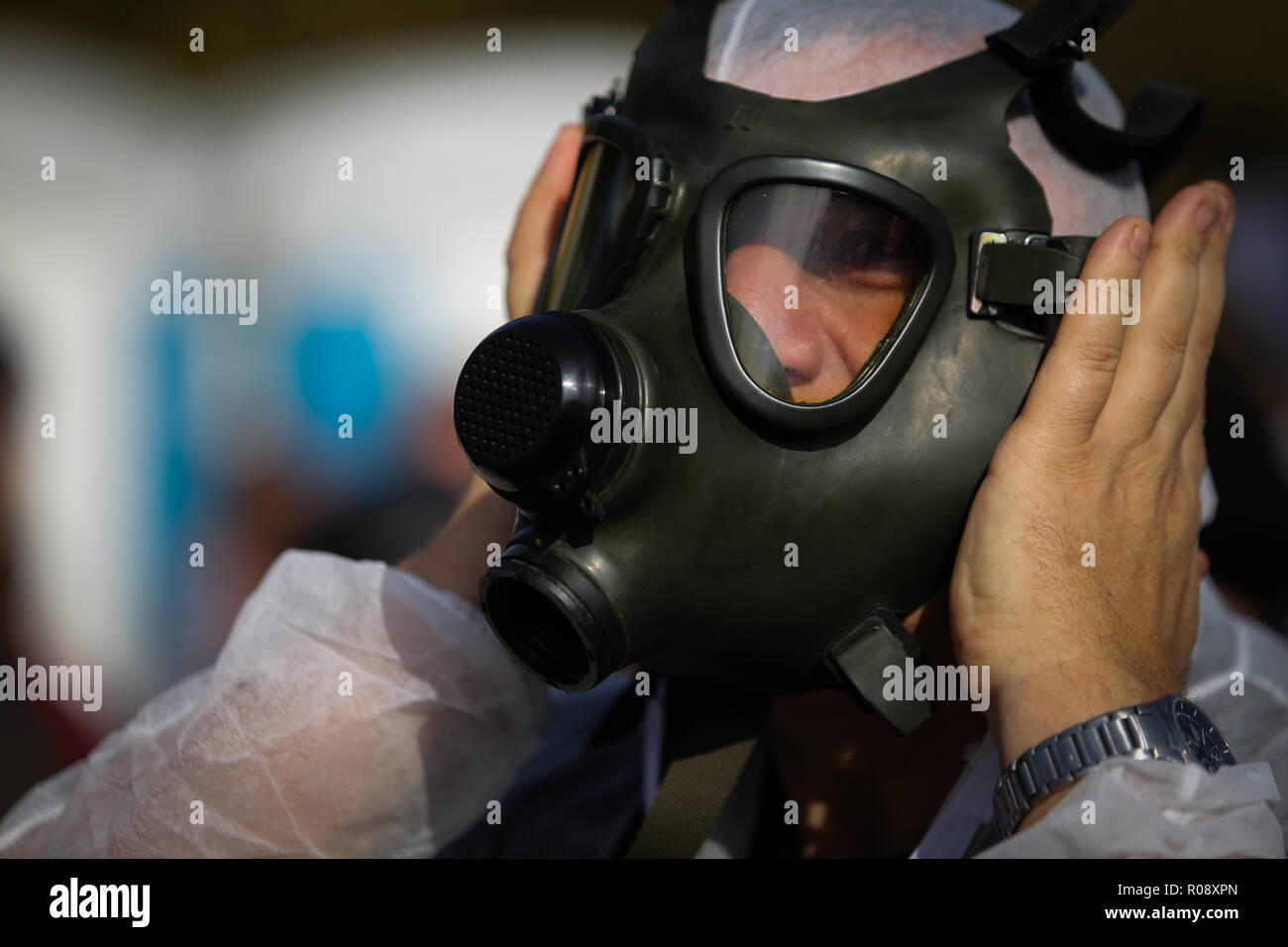 Vet doctor wearing a protective suit puts on a gas mask - Stock Image