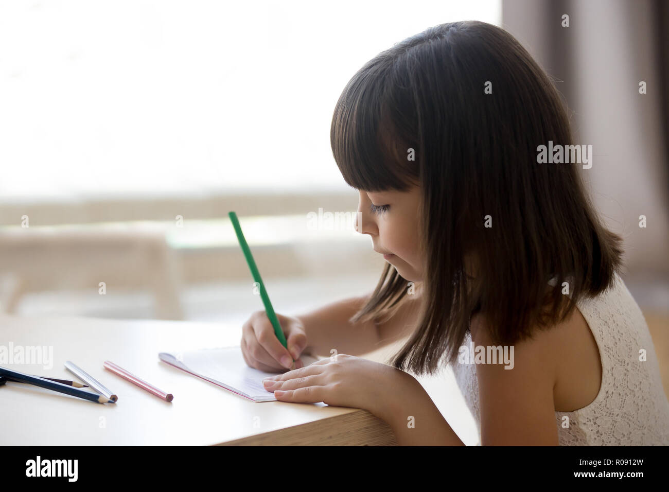 Little girl draws on paper sitting at table - Stock Image