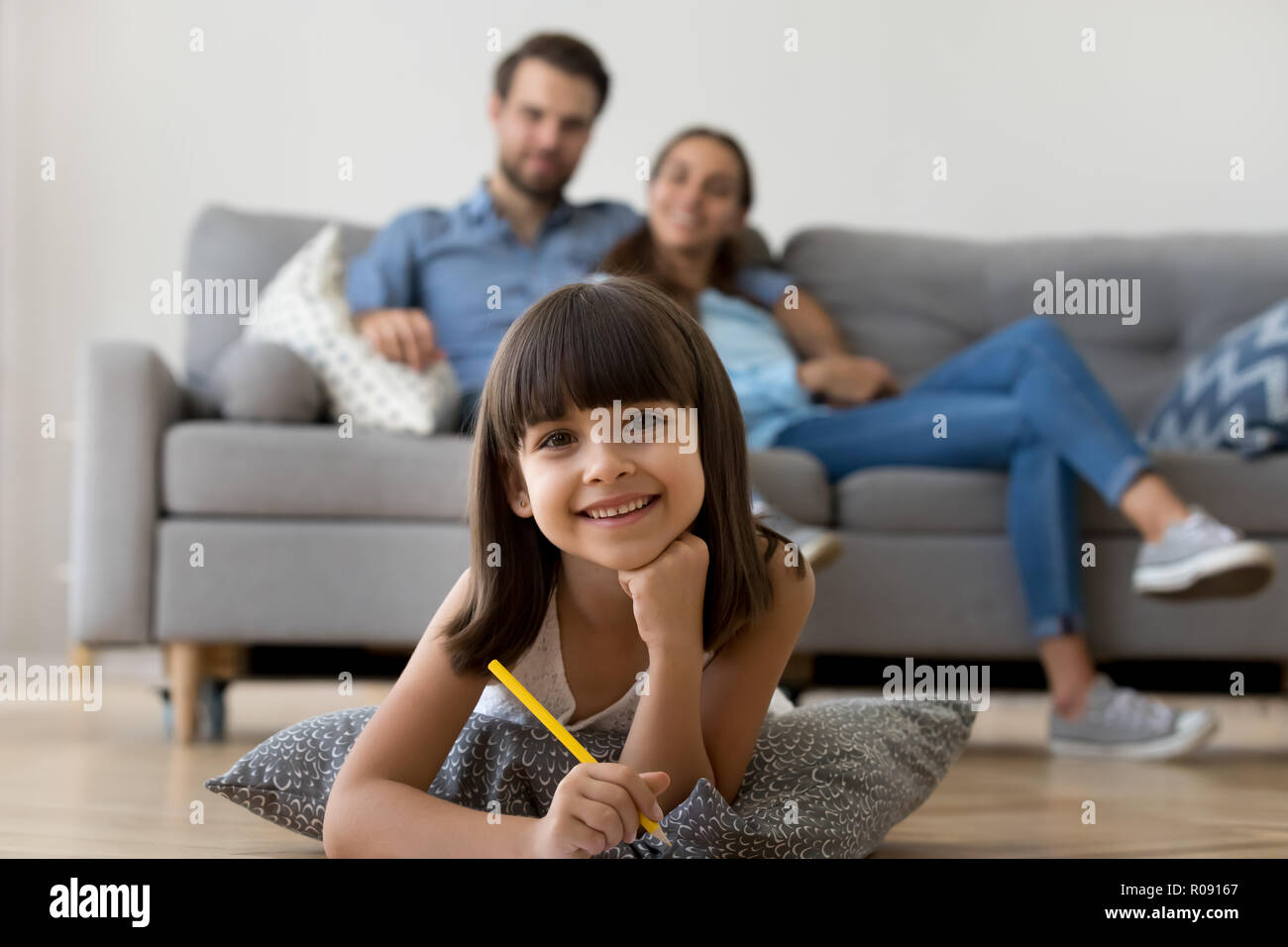 Daughter looking at camera lying on floor drawing holding pencil - Stock Image