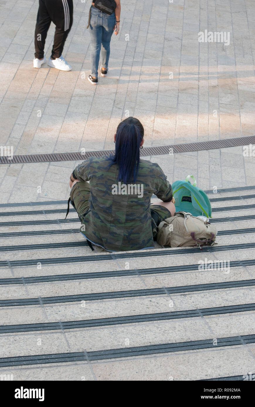 Young girl wearing camouflage sitting on steps searching web, listening to music watching at another girl and a boy, Love triangle choice concept. - Stock Image