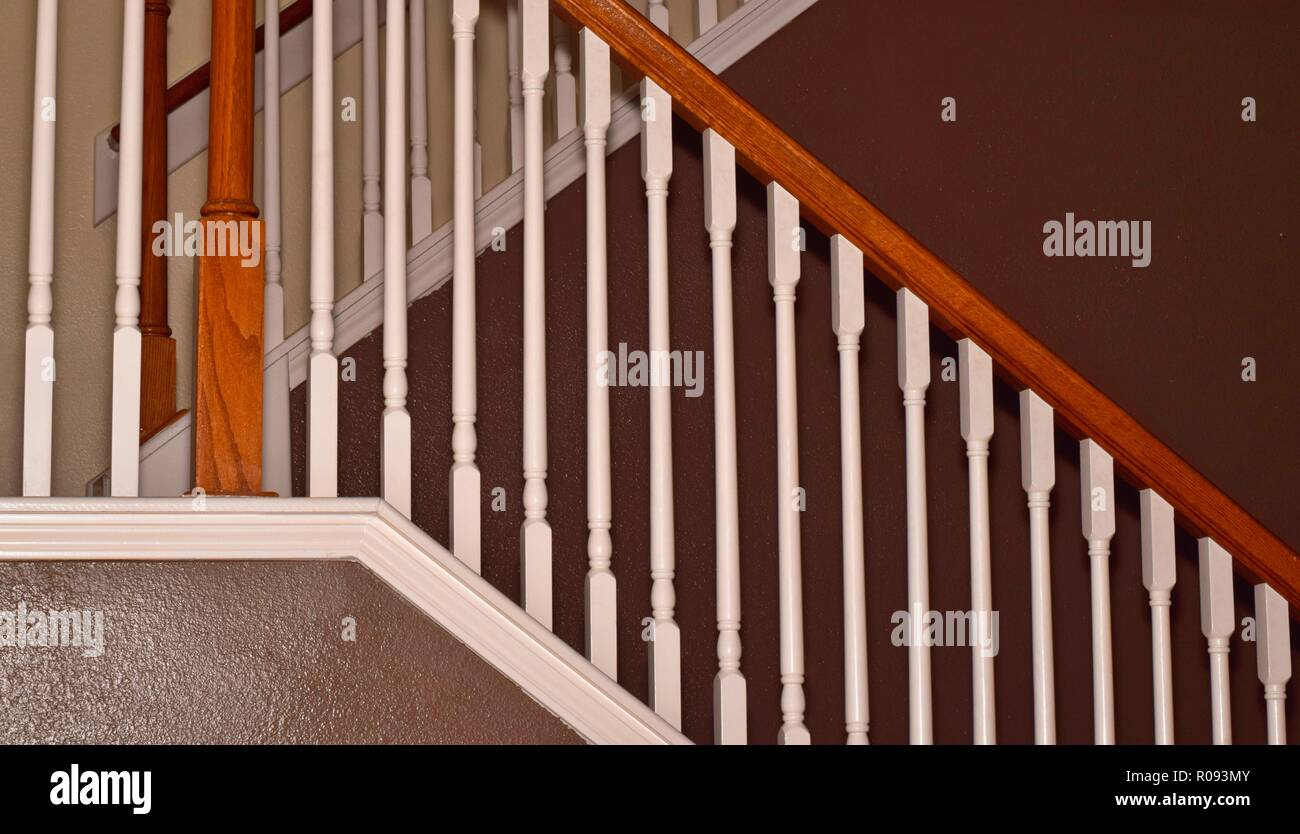Side-view of a home staircase with white railings and brown painted walls with a focus on diagonal lines. - Stock Image