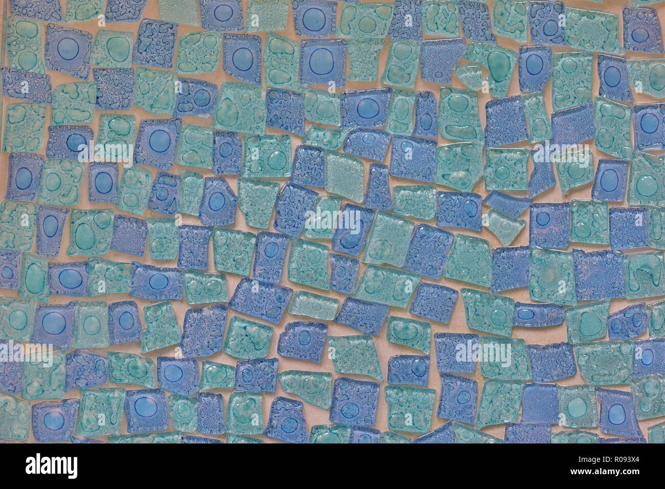 A mosaic pattern of uneven tiles with two-tone blues and a glossy finish. - Stock Image