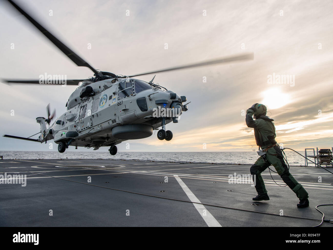 A Royal Netherlands Navy NH-90 takes off from HNLMS De Ruyter duirng NATO exercise Trident Juncture on October 31, 2018.  Trident Juncture 18 is designed to ensure that NATO forces are trained, able to operate together and ready to respond to any threat from any direction. Trident Juncture 18 takes place in Norway and the surrounding areas of the North Atlantic and the Baltic Sea, including Iceland and the airspace of Finland and Sweden. With around 50,000 participants from 31 nations, Trident Juncture 2018 is one of NATO's largest exercises in recent years. More than 250 aircraft, 65 ships an Stock Photo