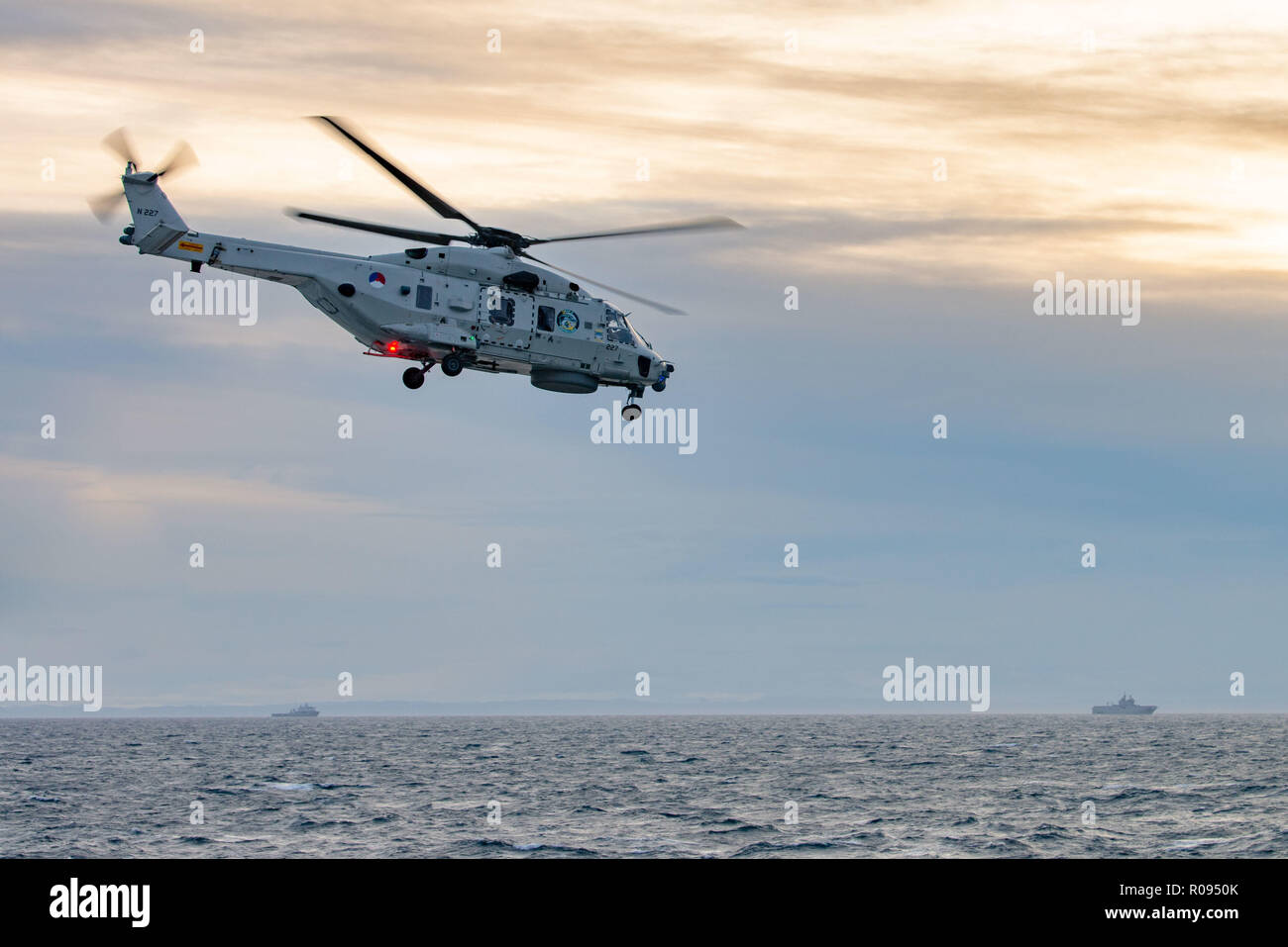 NORWAY, Oct. 31 2018. GEN. SNMG2 VESSELS ESCORT AMPHIBIOUS TASK GROUP.  A Royal Netherlands Navy NH-90 takes off from HNLMS De Ruyter duirng NATO exercise Trident Juncture on October 31, 2018.    Trident Juncture 18 is designed to ensure that NATO forces are trained, able to operate together and ready to respond to any threat from any direction. Trident Juncture 18 takes place in Norway and the surrounding areas of the North Atlantic and the Baltic Sea, including Iceland and the airspace of Finland and Sweden.     With around 50,000 participants from 31 nations Trident Juncture 2018 is one of  Stock Photo
