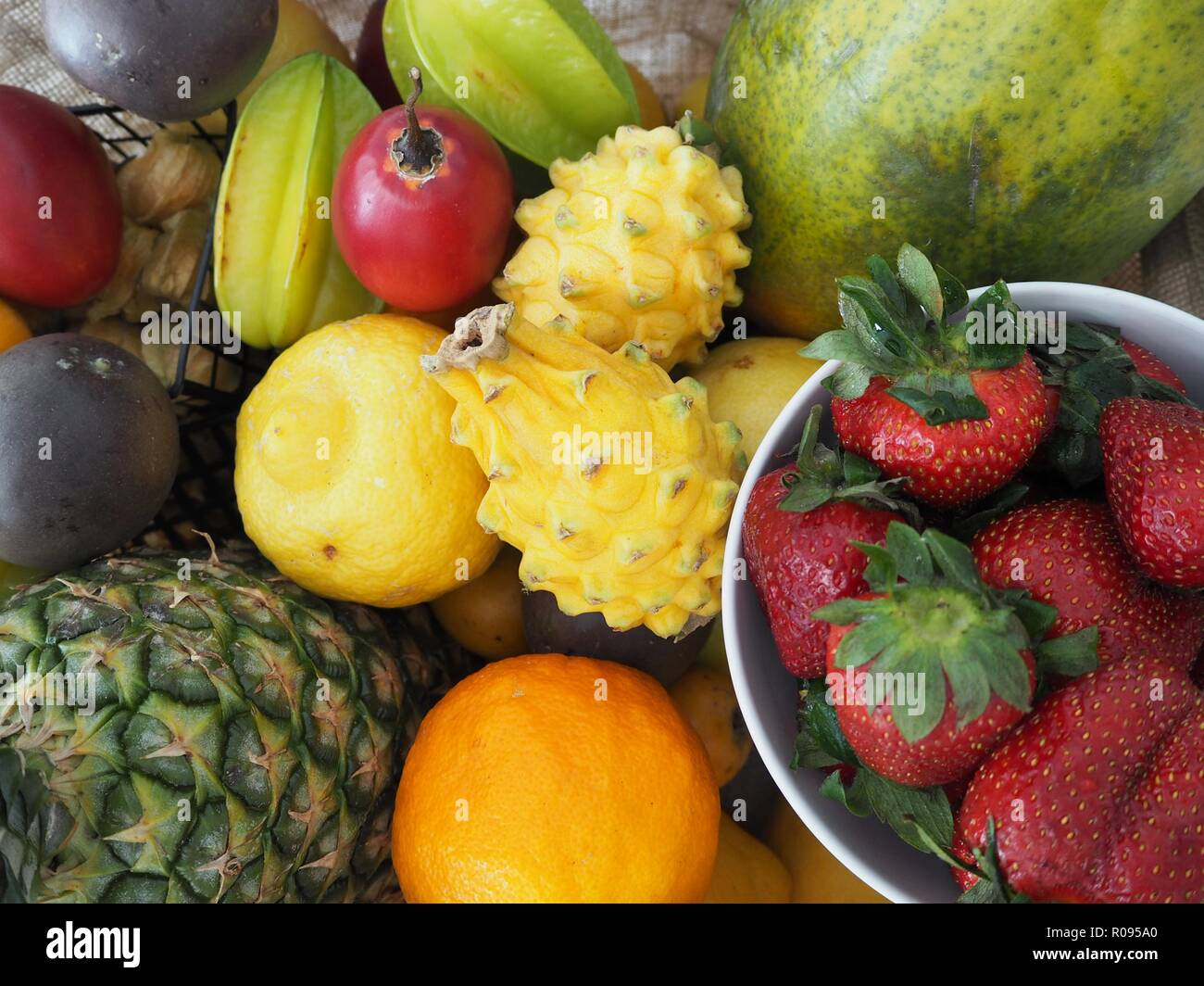 Various colorful tropical fruit, selection in wooden tray over, top view, pineapple, strawberry, dragon fruit, orange, lemon, papaya, star fruit,vegan Stock Photo