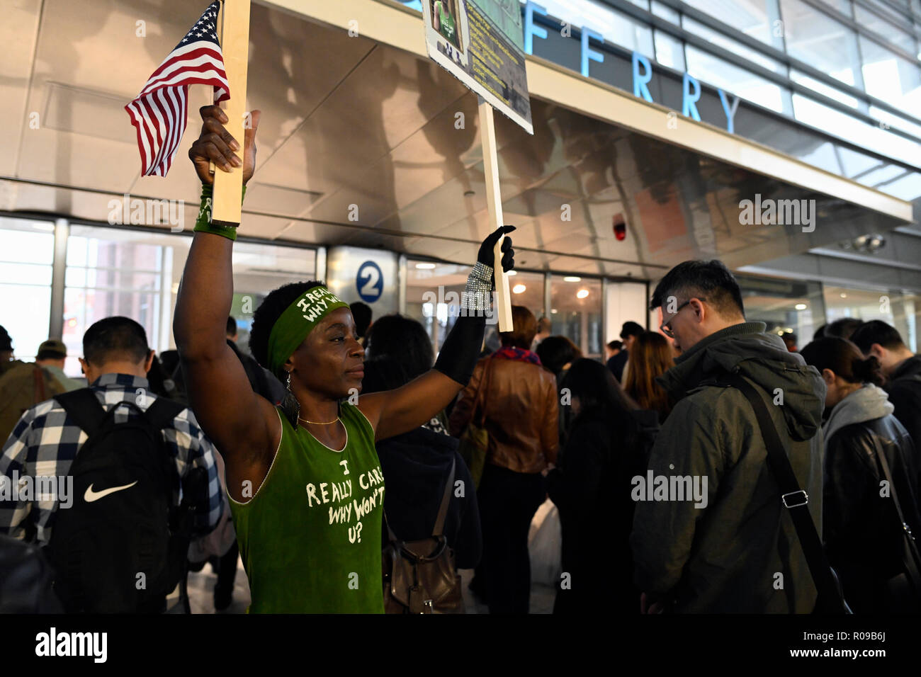 New York, USA. 2 November 2018.  Activist Patricia Okoumou, who climbed the pedestal of the Statue of Liberty on July 4, urges morning commuters at the Staten Island Ferry Terminal to vote in the mid-term elections on Tuesday.  Okoumou faces trial in federal court in Manhattan on  December 17 on charges related to her act of civil disobedience in which she climbed the pedestal of the Statue of Liberty to protest against Trump administration immigration policies.  Okoumou is a native of the Republic of the Congo. Credit: Joseph Reid/Alamy Live News Stock Photo