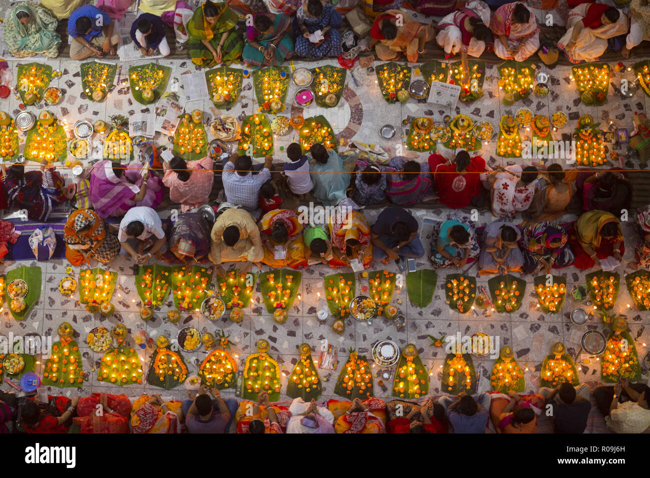 Dhaka, Bangladesh. 3rd Nov, 2018. DHAKA, BANGLADESH - NOVEMBER 03 : Hundreds of Hindu devotees sits with Prodip and prays to God in front of Shri Shri Lokanath Brahmachari Ashram temple during the Kartik Brati or Rakher Upobash in Dhaka, Bangladesh on November 03, 2018.Every year thousands of Hindu devotees gather in front of Shri Shri Lokenath Brahmachari Ashram temple for the Kartik Brati or Rakher Upobash religious festival in Dhaka, Bangladesh. Faithful sit in front of candles light ( named locally as Prodip ) and absorb in prayer. Credit: ZUMA Press, Inc./Alamy Live News - Stock Image