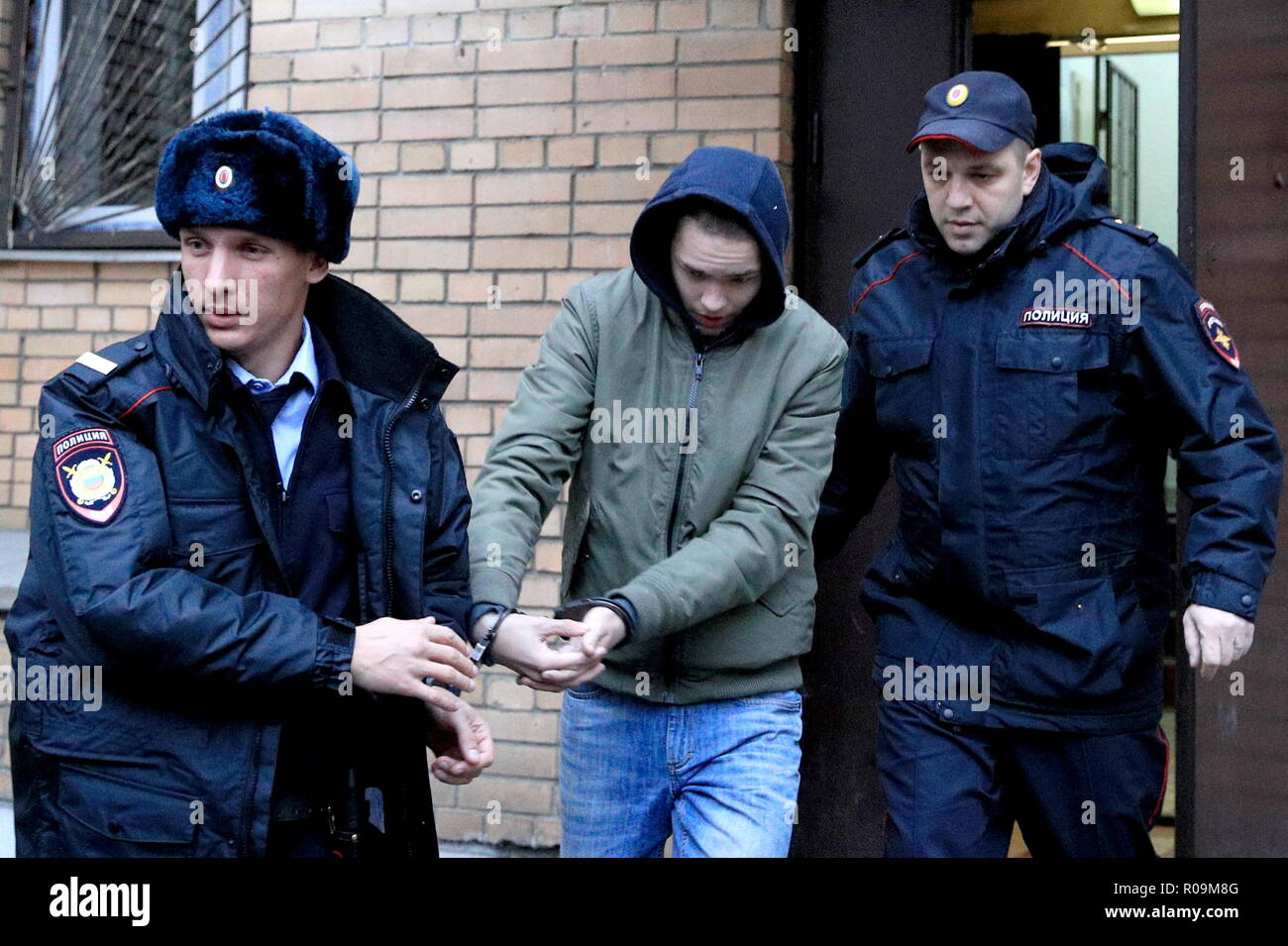 MOSCOW, RUSSIA - NOVEMBER 3, 2018: Police officers lead a teenager (C) who was detained 2 November 2018 after police seized an explosive device and related materials in his home; Moscow's Presnensky District court has extended the pre-trial detention of the teenager by 72 hours; according to the investigators, the teenager is suspected of having being in contact with a 17-year-old man who allegedly brought and was killed by an explosive device at an office of the Russian Federal Security Service (FSB) in Arkhangelsk on 31 October 2018. Sergei Bobylev/TASS Stock Photo