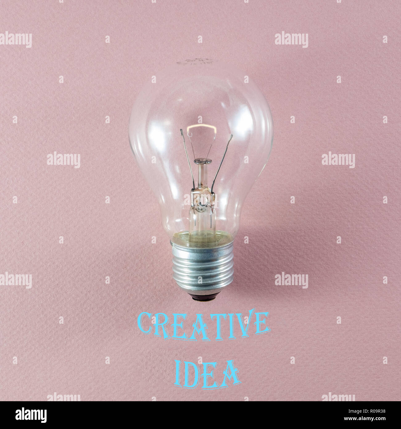 Creative idea and innovation concept via lit bulb on pink background and relevant text in modern font Stock Photo