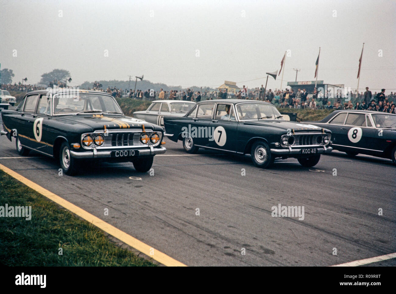 Motor racing at the Brands Hatch circuit in England in the early 1960s. Shown are two Ford Zodiac cars, number 6 and 7. Photo of the starting grid, just  prior to the race starting. - Stock Image