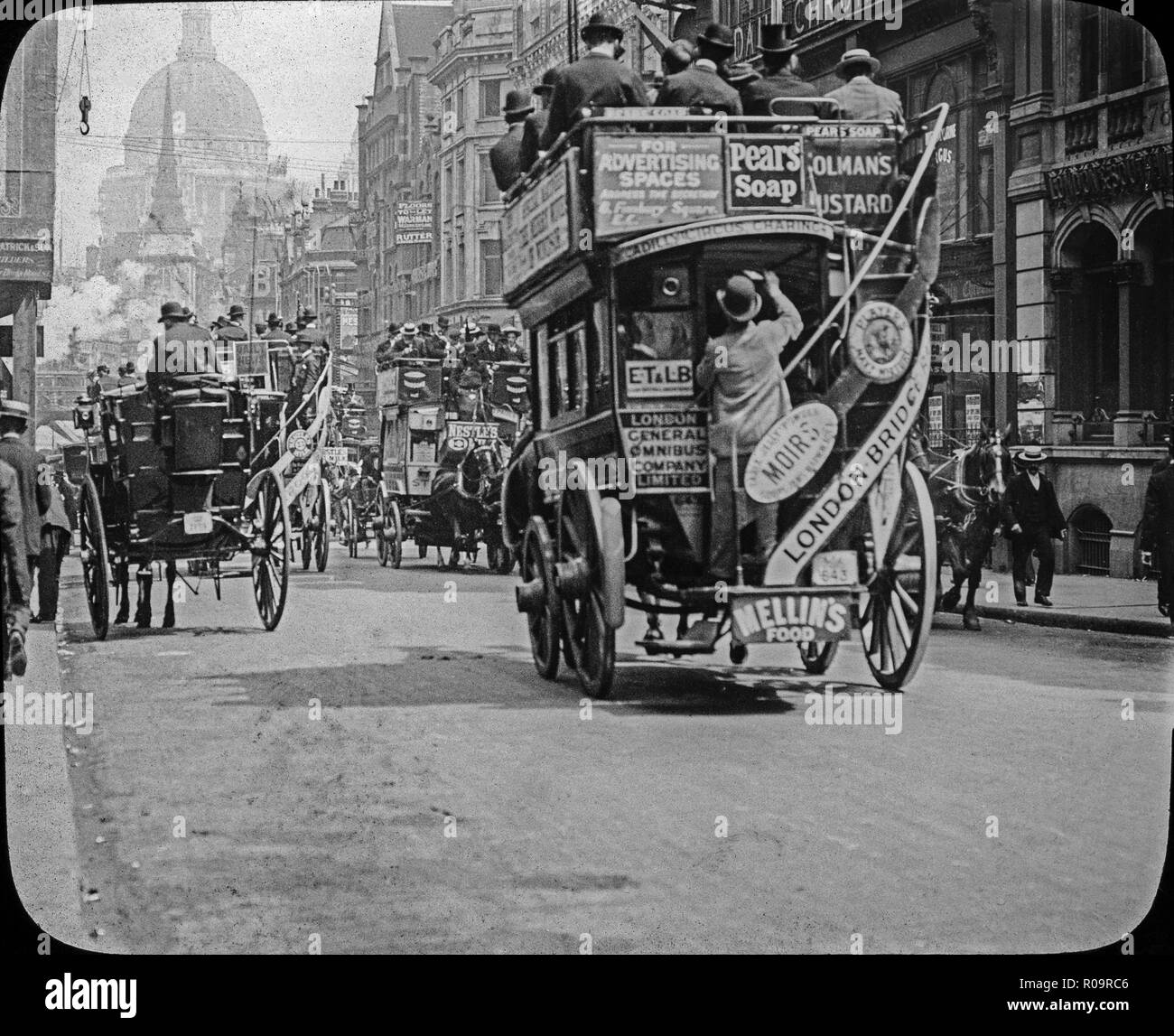 Late 19th century Victorian black and white photograph taken on the streets of London, showing horse drawn omnibuses, covered on adverts,  carrying many passengers, plus street crowded with people. Shop signs are also visible. - Stock Image