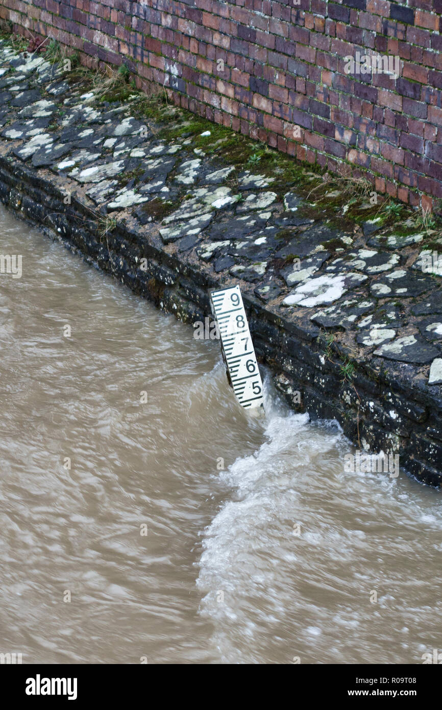 Presteigne, Powys, mid Wales, UK. The River Lugg in winter, at high flood level beneath the town's old 17c stone bridge Stock Photo