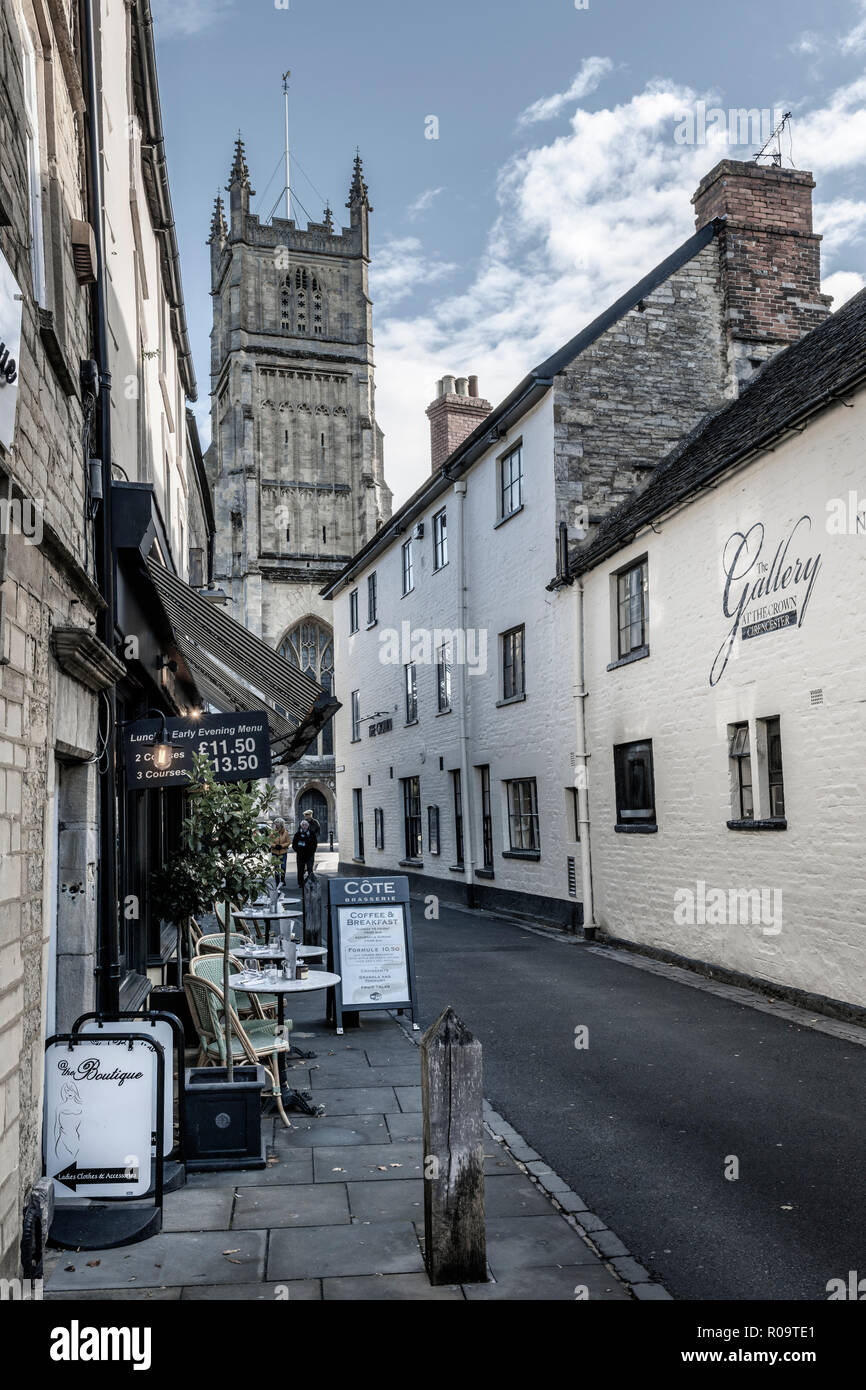The Parish Church of St. John the Baptist as viewed from Black Jack Street in the Roman town of Cirencester (Corinium) in Gloucestershire, England. - Stock Image
