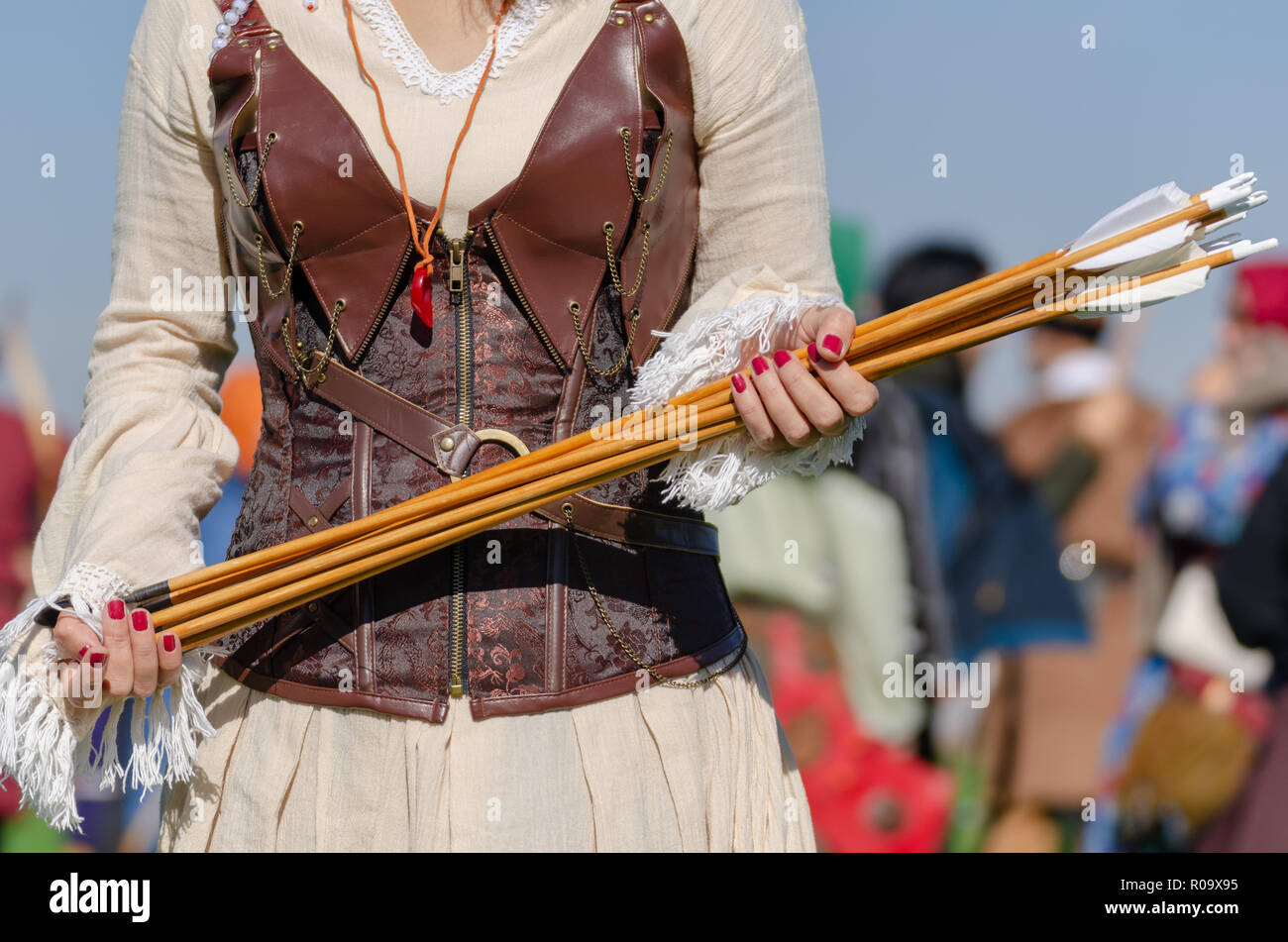 Traditional Archery Competitions. Traditional archery equipment.Female archer is holding arrows in her hand. - Stock Image