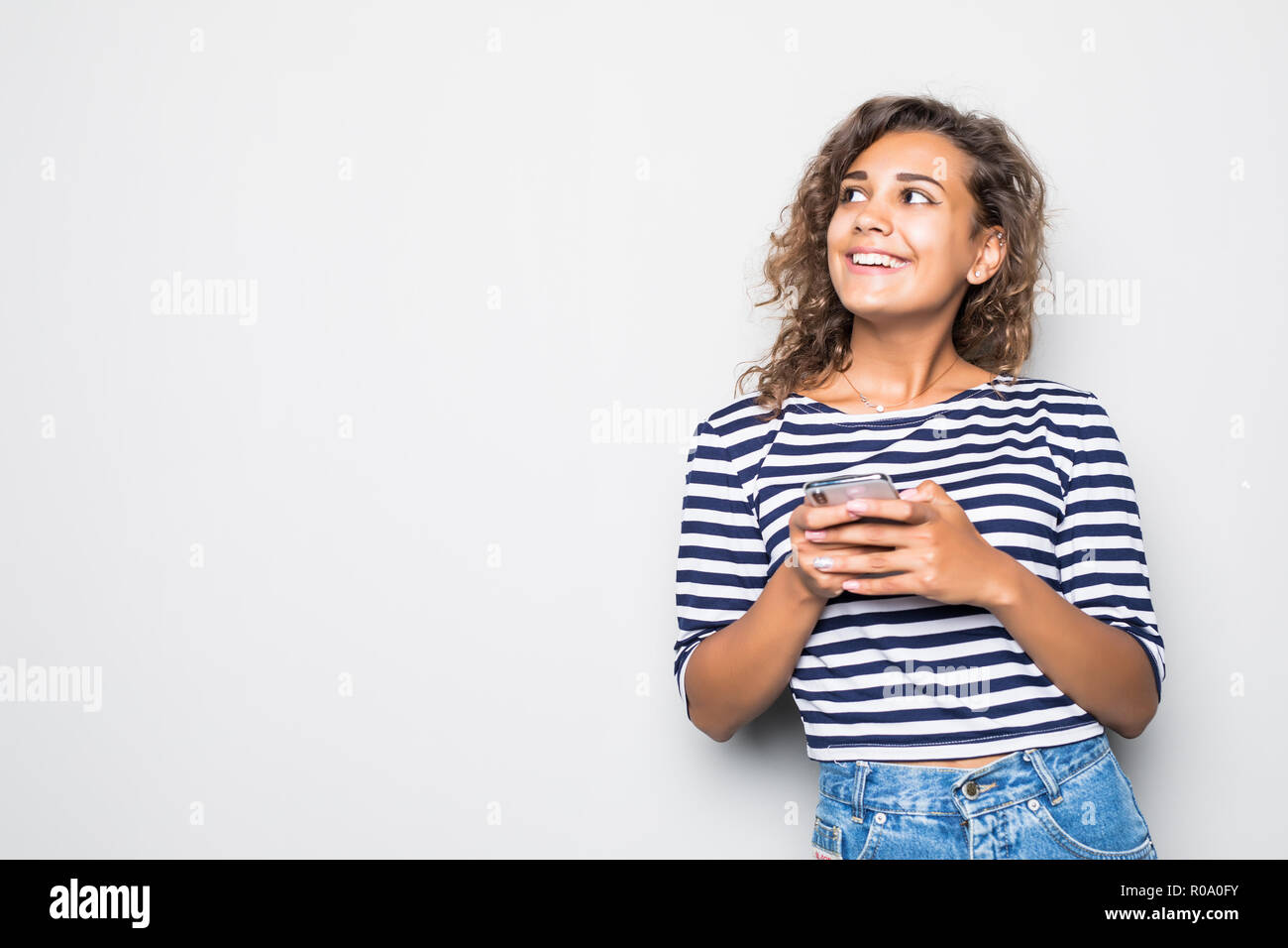 Cheerful mulatto woman tuping on the phone isolated on gray background Stock Photo