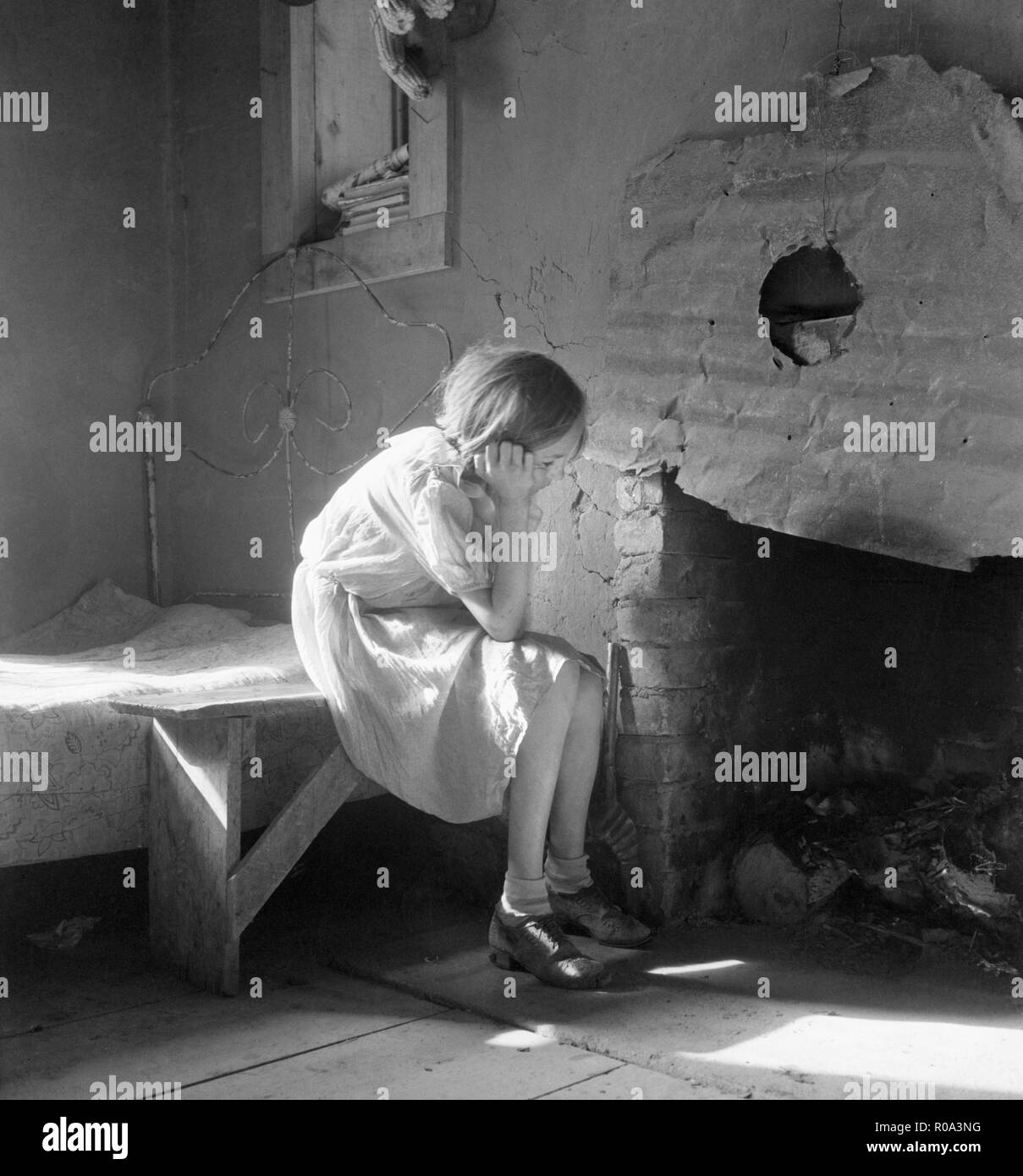 Resettled Farm Child from Taos Junction to Bosque Farms Project, Portrait Sitting near Fireplace, Mills, New Mexico, USA, Dorothea Lange, Farm Security Administration, December 1935 - Stock Image