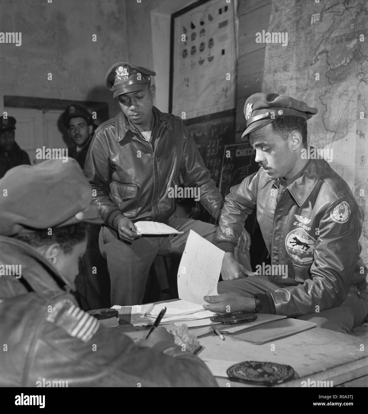 Tuskegee Airmen attending Briefing at Air Base, Woodrow W. Crockett, standing at center, Edward C. Gleed, Lawrence, KS, Class 42-K, Group Operations Officer, Seated on Right, and Unidentified Airman Seated on Left, Ramitelli, Italy, Toni Frissell, March 1945 - Stock Image