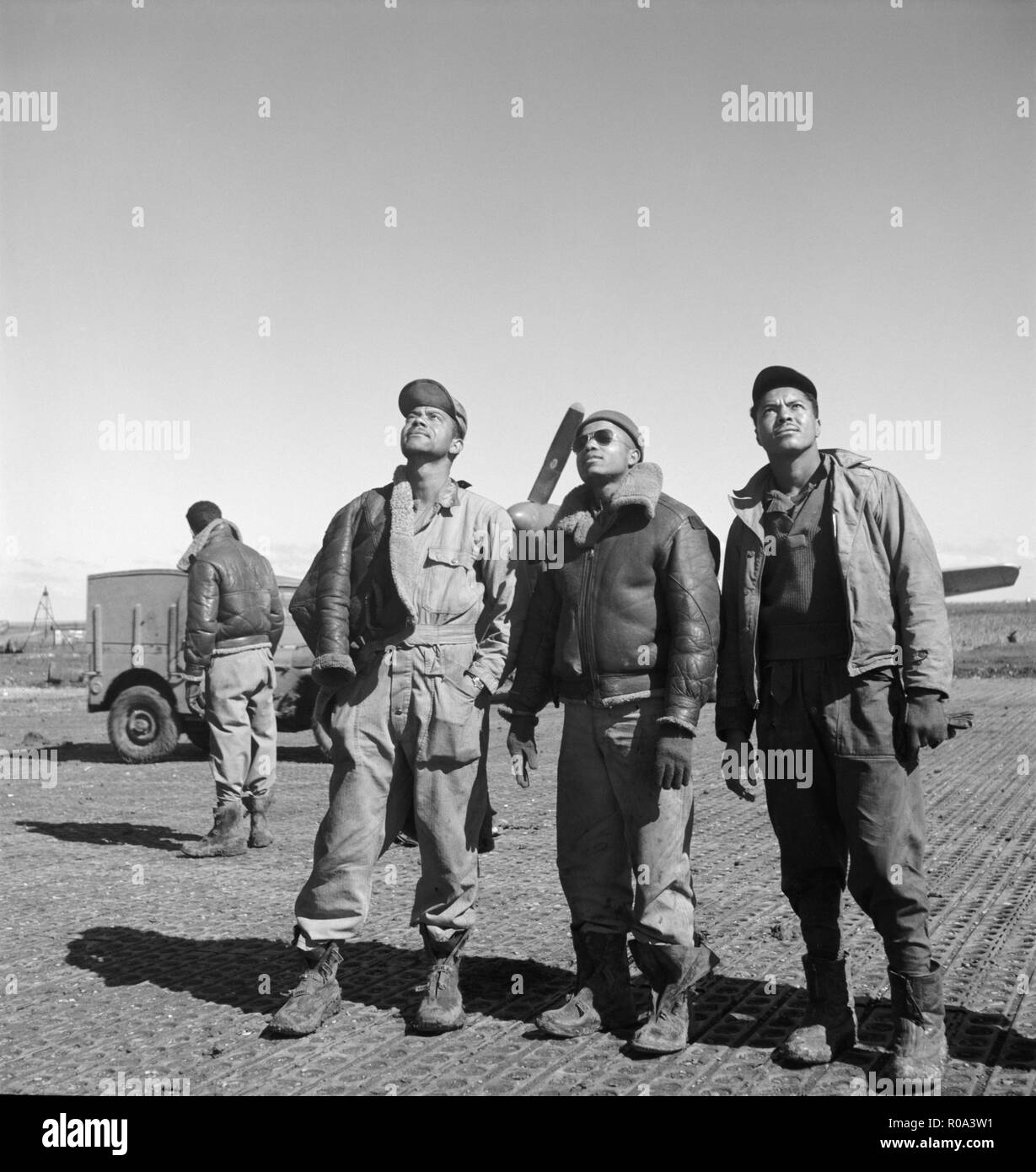 Three Tuskegee Airmen looking Up at Air Base, Ramitelli, Italy, Toni Frissell, March 1945 - Stock Image