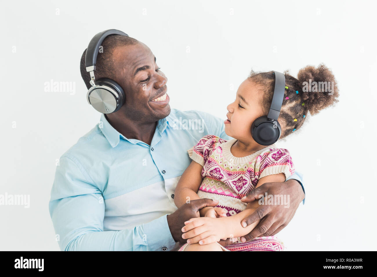 Cute Little Girl And Her Dad Are Listening To Music With Headphones