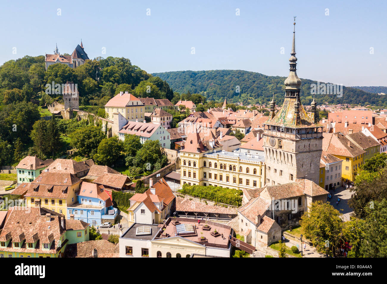 Green hills, spires and red tiled roofs of Walled old town of Sighisoara (Sighishoara), Mures, Transylvania, Romania. The Clock Tower of Sighișoara. - Stock Image