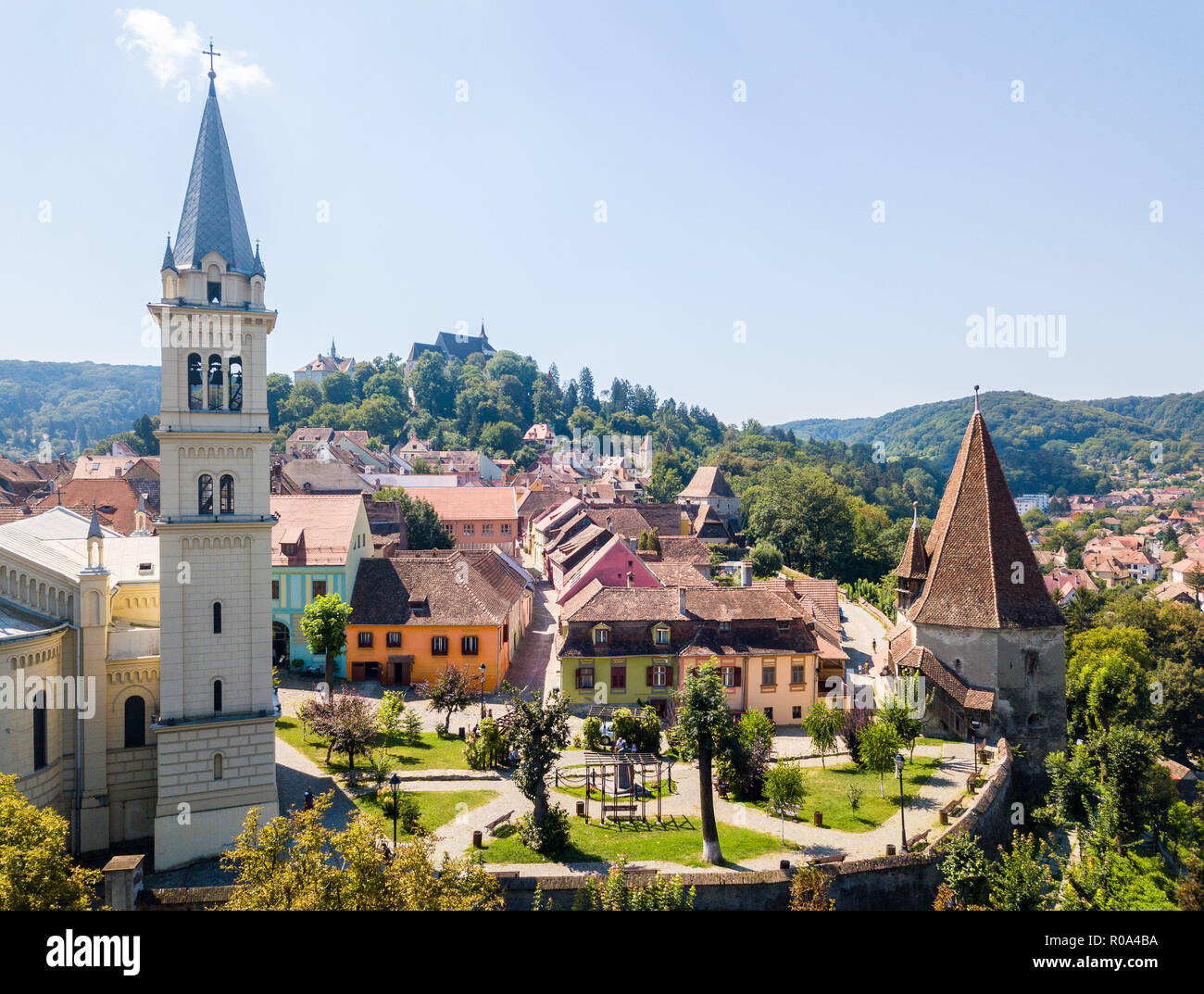 Spires and red tiled roofs of Walled old town of Sighisoara, Transylvania, Romania. Bell tower of St. Joseph's Cathedral and Bootmakers' Tower - Stock Image