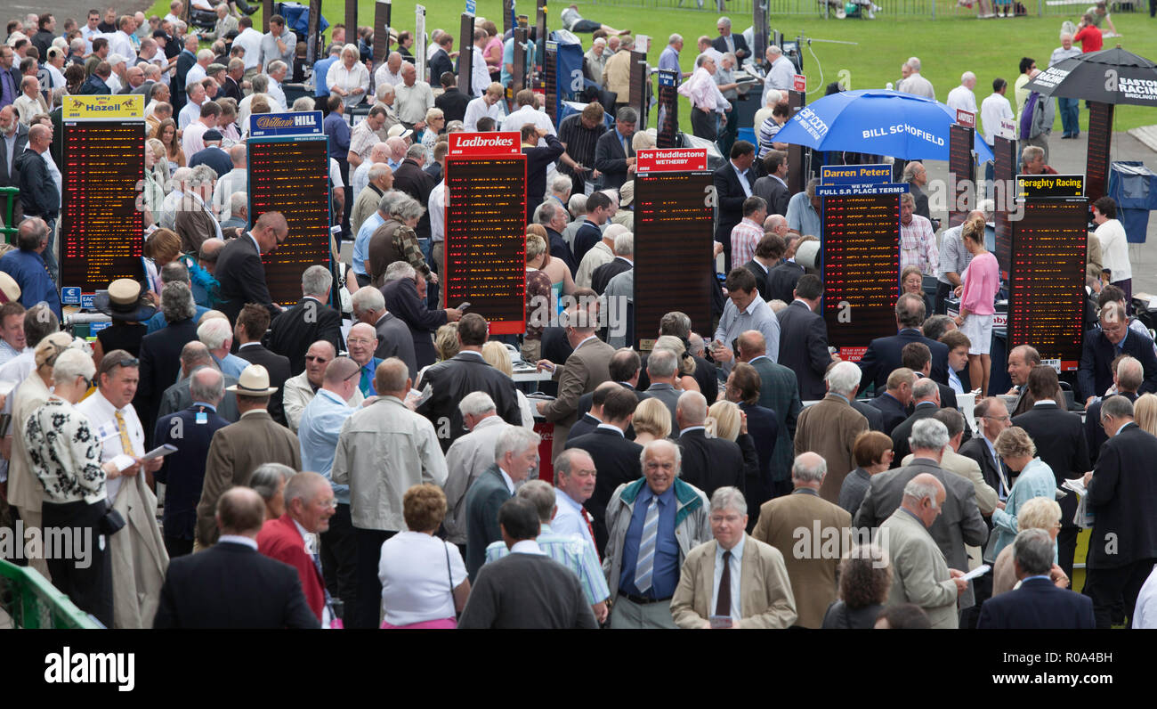 On course bookmakers and crowds of spectators at a race meeting at Thirsk racecourse in North Yorkshire - Stock Image