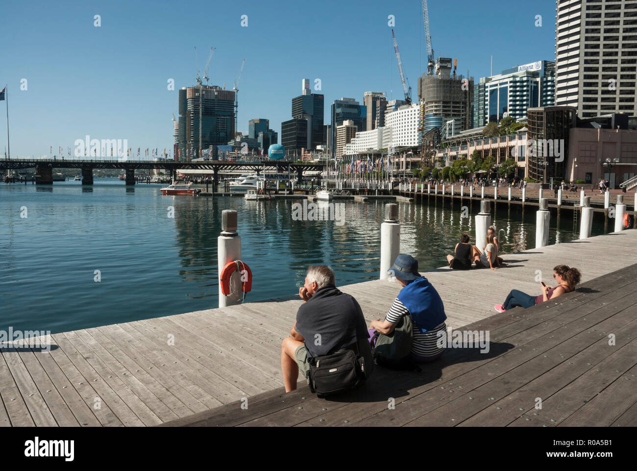 People resting on a board walk in the sunshine, with the quayside, boats and buildings of Darling Harbour. - Stock Image