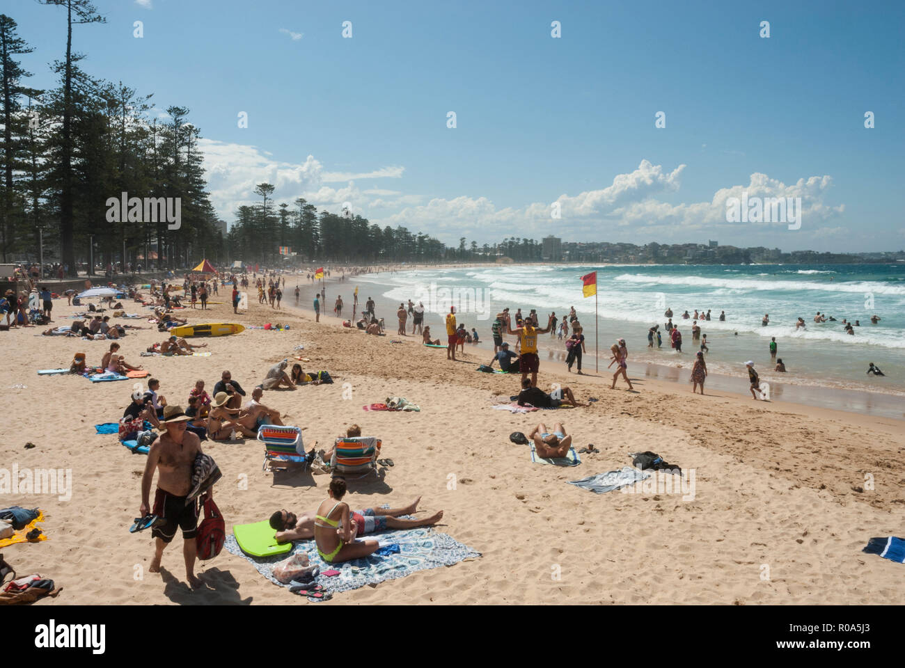 View along the golden sands of Manly Beach, Sydney, Australia with holidaymakers sunbathing, swimming and surfing in the spring sunshine. Stock Photo