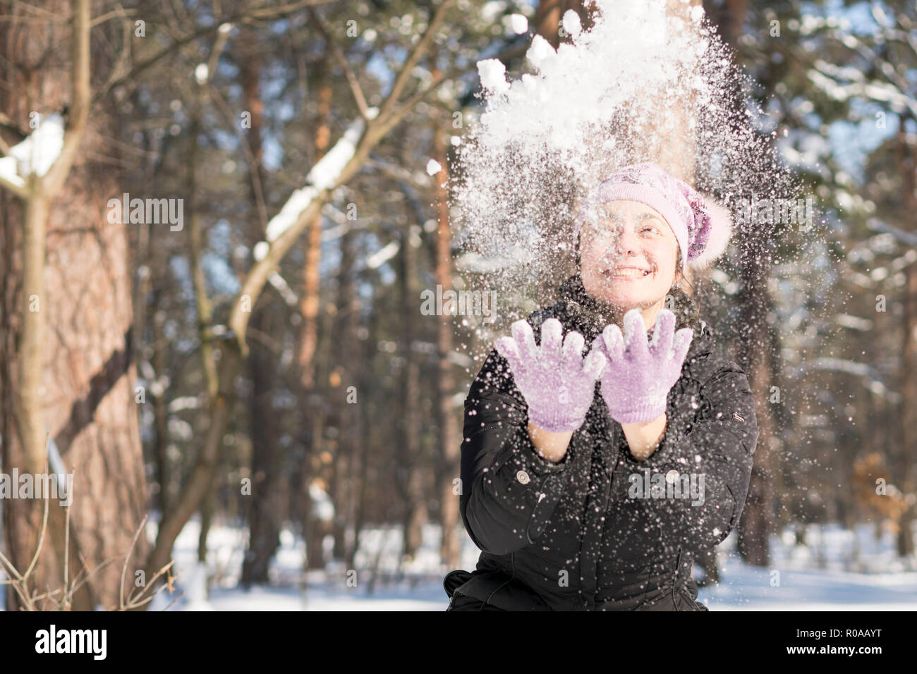 Girl throws snow up. Portrait of the beautiful girl throwing snow in the winter. Happy young woman plays with a snow in sunny winter day.Stock Photo