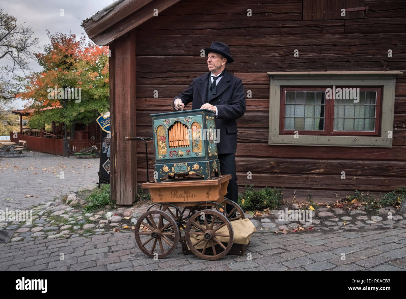 Skansen open air museum, Djurgarden, Sweden. Re-enactor plays a Raffin organ illustrating pre industrial life in early towns and villages. - Stock Image