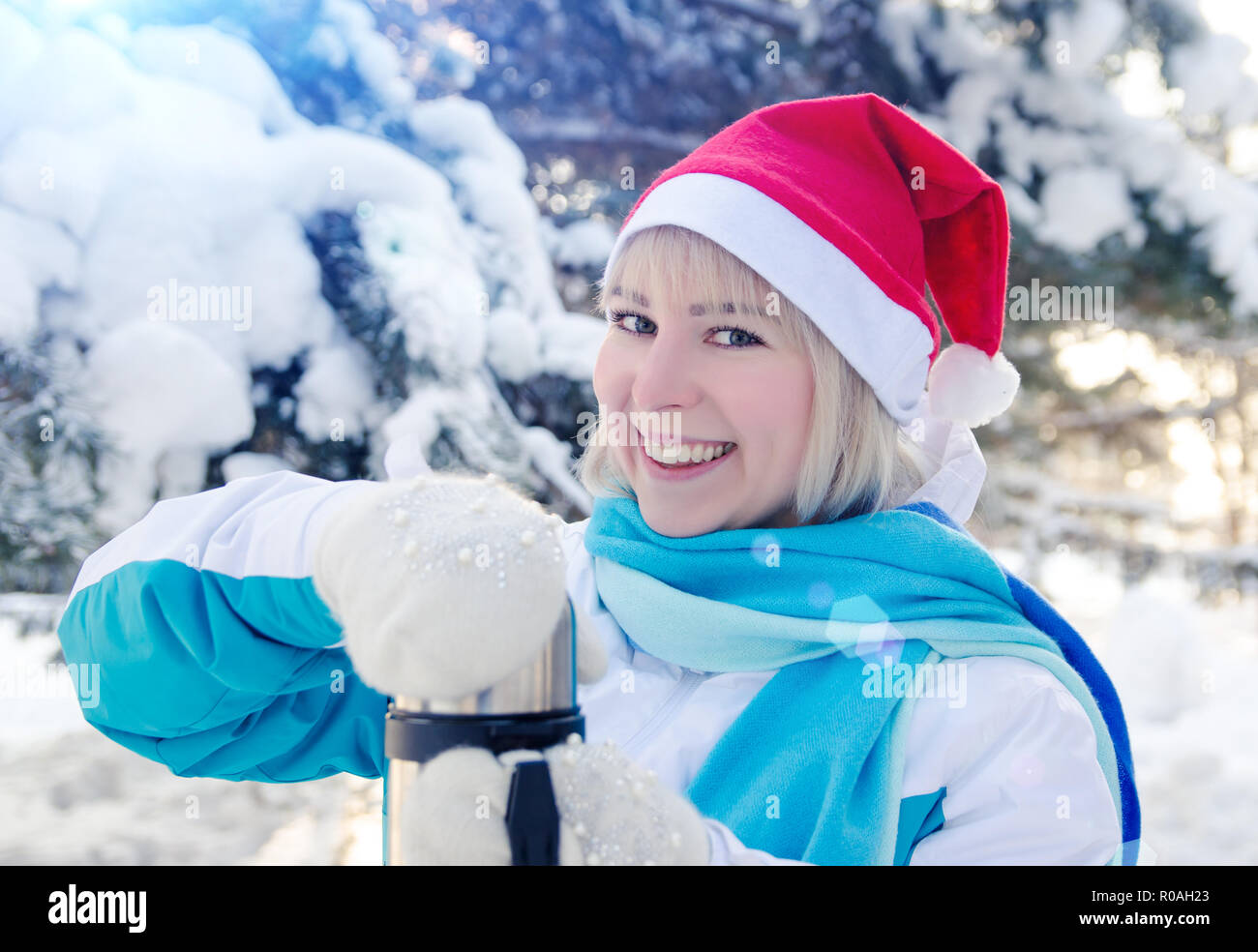 Beautiful Smiling Blonde Girl In A Red Christmas Hat Opens A Thermos With Hot Tea
