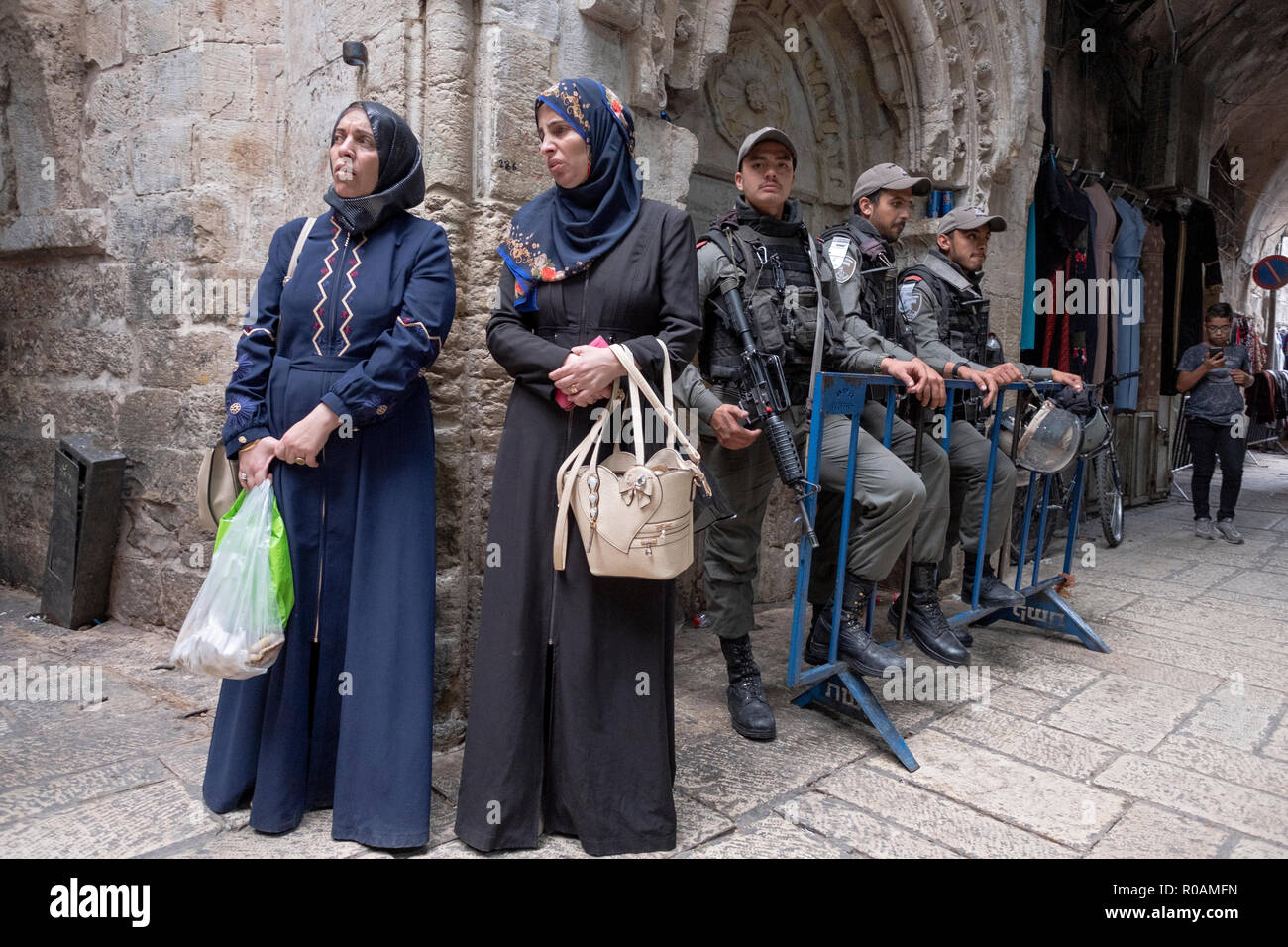 Armed Israeli soldiers in close proximity to Muslim Arab women shoppers in the Old City of Jerusalem in Israel. - Stock Image