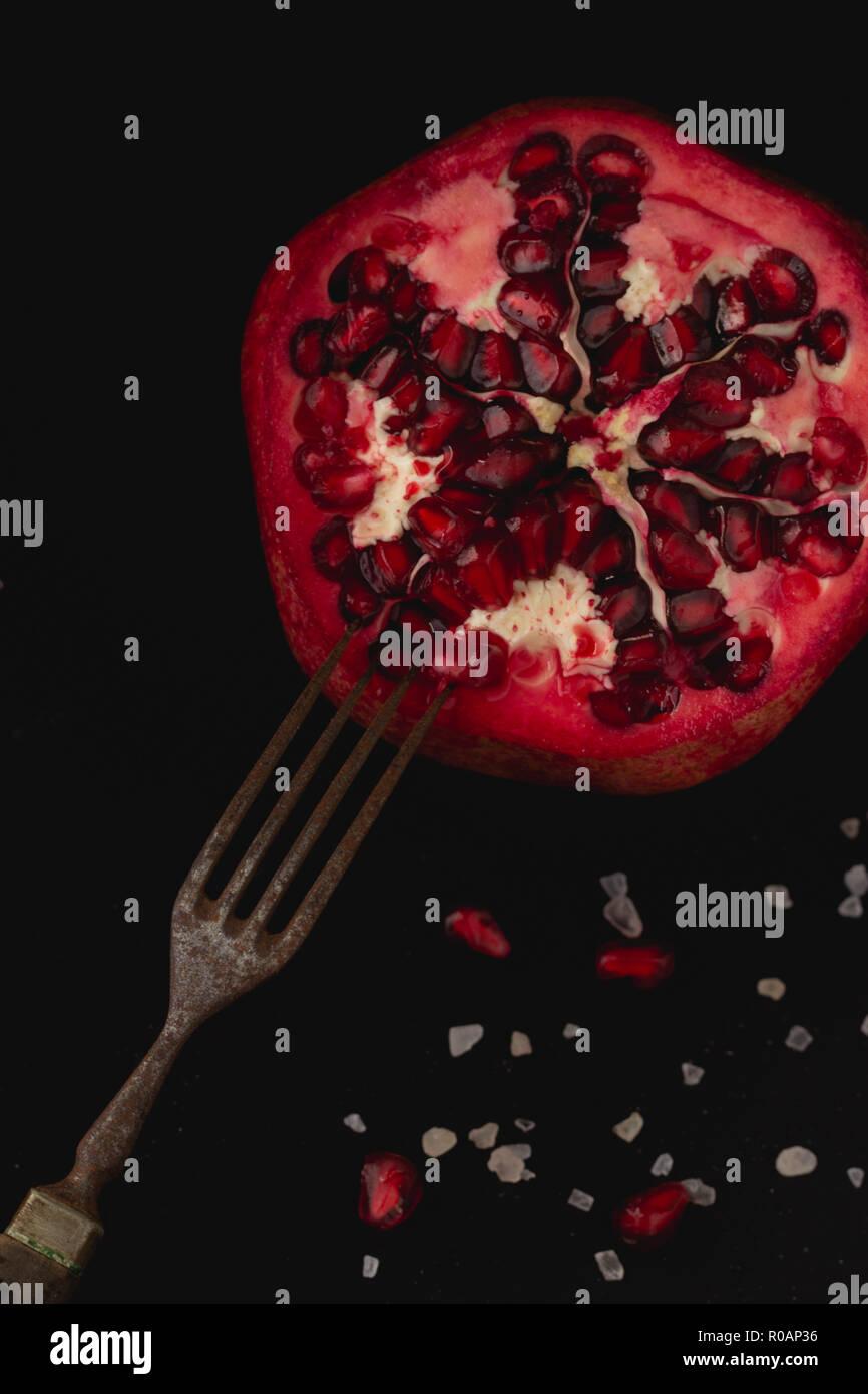 Frischer Granatapfel mit Salz und rostiger Gabel auf dunklem Untergrund - Stock Image