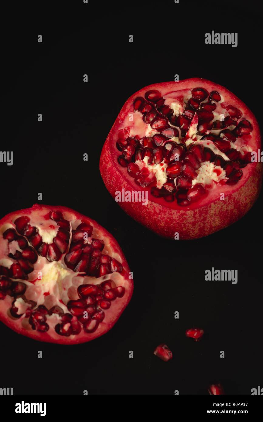 Frischer Granatapfel auf dunklem Untergrund und Hintergrund - Stock Image