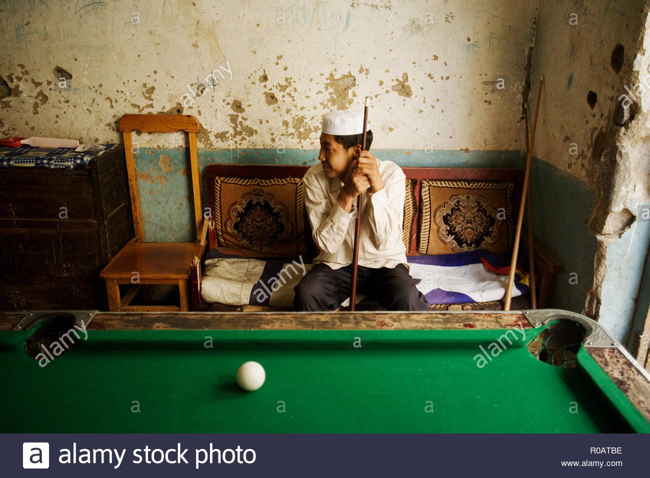 A young muslim boy at a pool hall - Stock Image