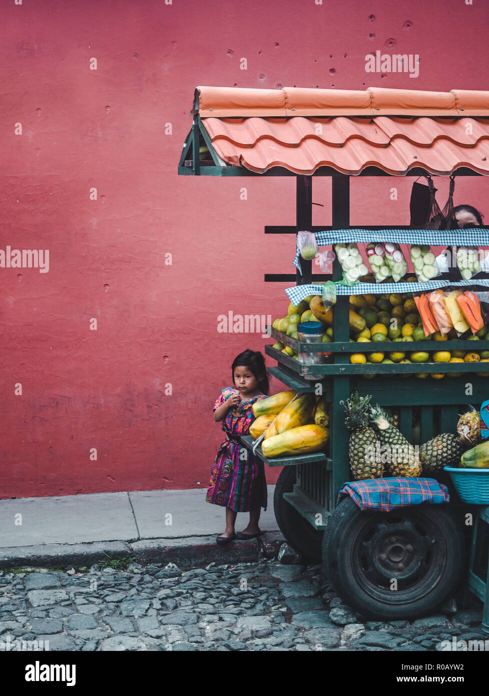 Small young Guatemalan girl in traditional Mayan dress hiding behind her family's fruit cart street stall - Stock Image