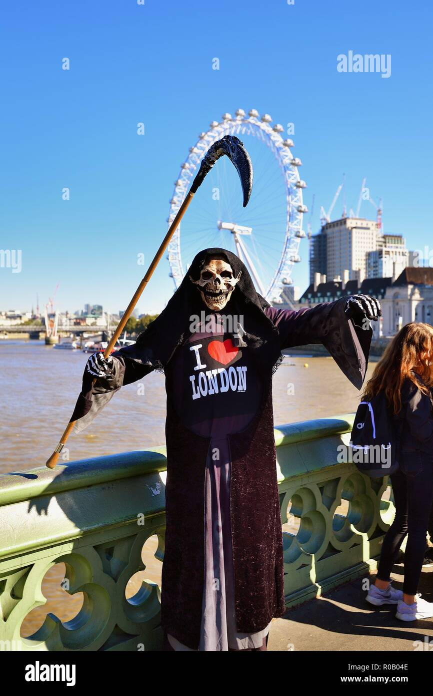 London, England, United Kingdom. A man in costume as the Grim Reaper entertains tourists on Westminster Bridge above the River Thames. - Stock Image