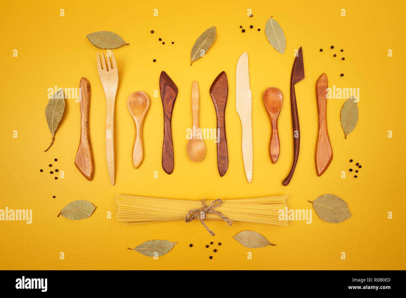 Handcrafted wooden utensils, pasta and spices on bright yellow background. - Stock Image
