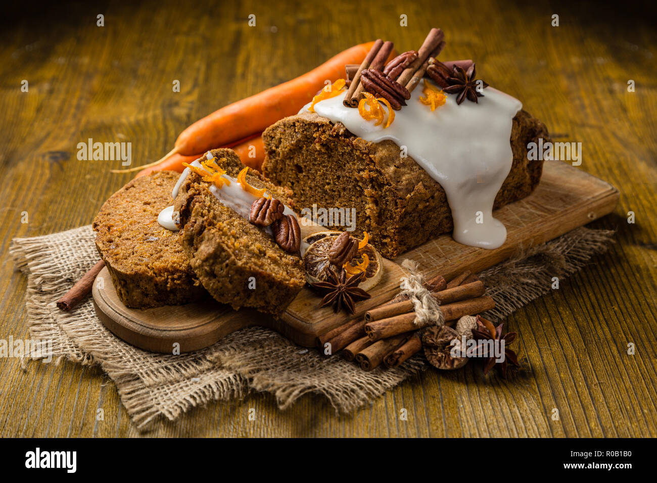 Carrot cake with autumn decorations, rustic wood background - Stock Image