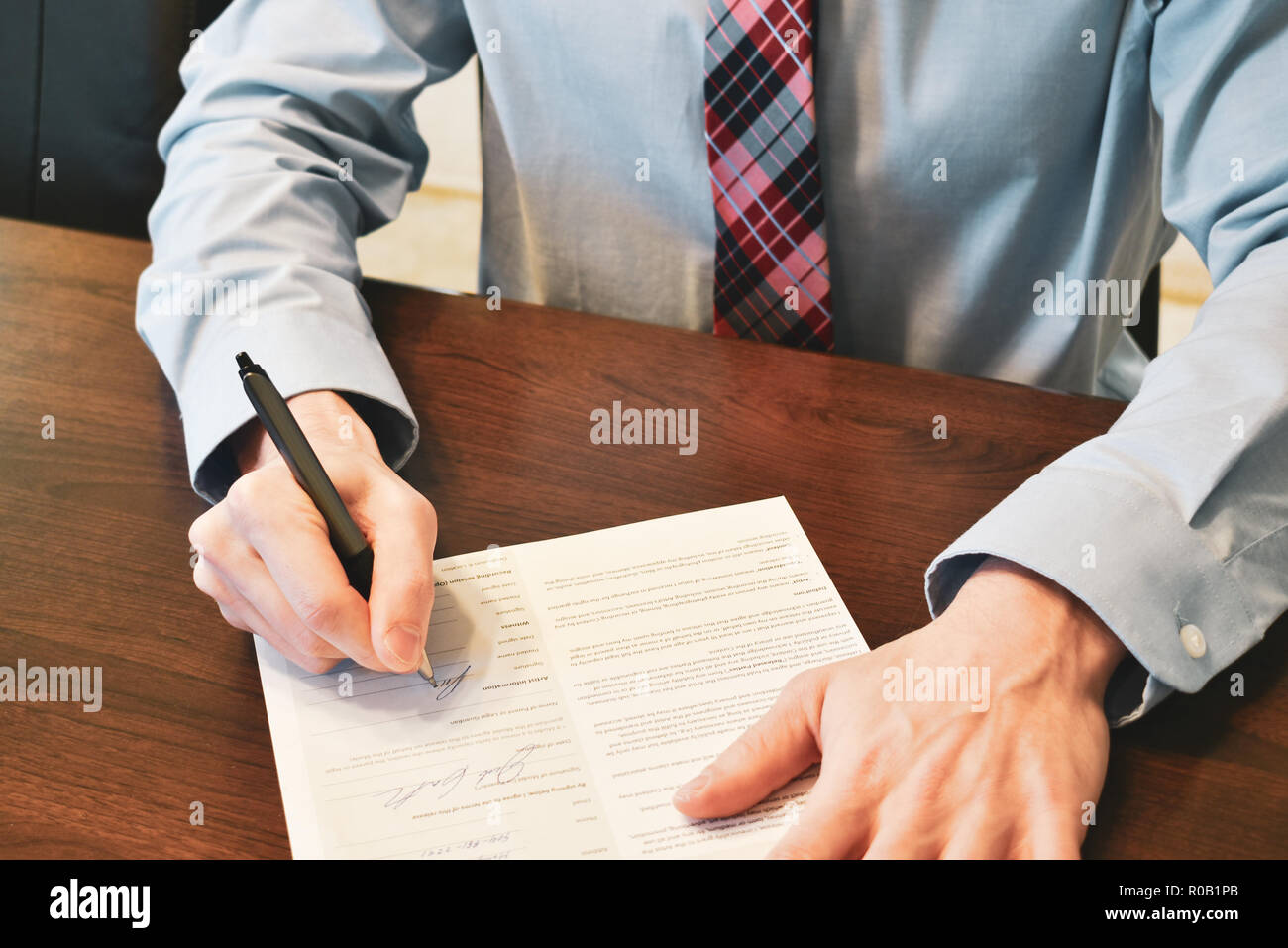 signing a paper at desk - Stock Image