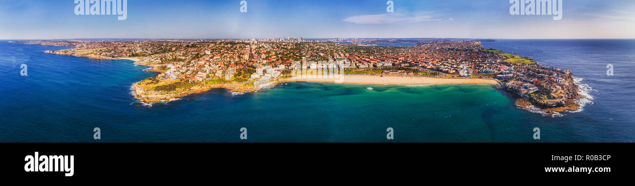 Coastline of SYdney's Eastern Suburbs around famous Bondi beach between sandstone cliff headlands seen from open see high in the air. - Stock Image