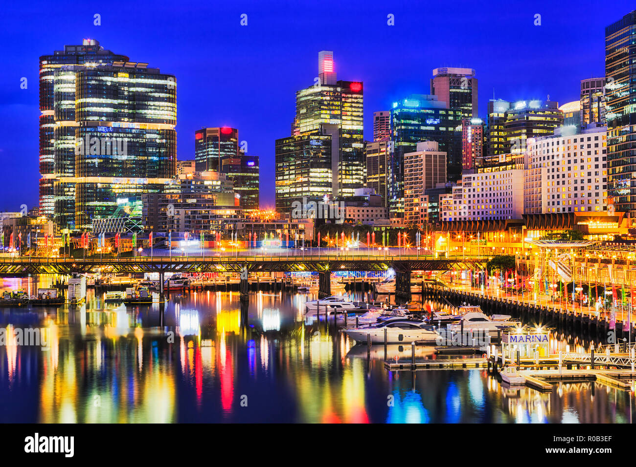 Waterfront of Sydney city CBD high-rise towers around Darling harbour with marina boats over Pyrmont bridge reflecting in still waters at sunset. - Stock Image