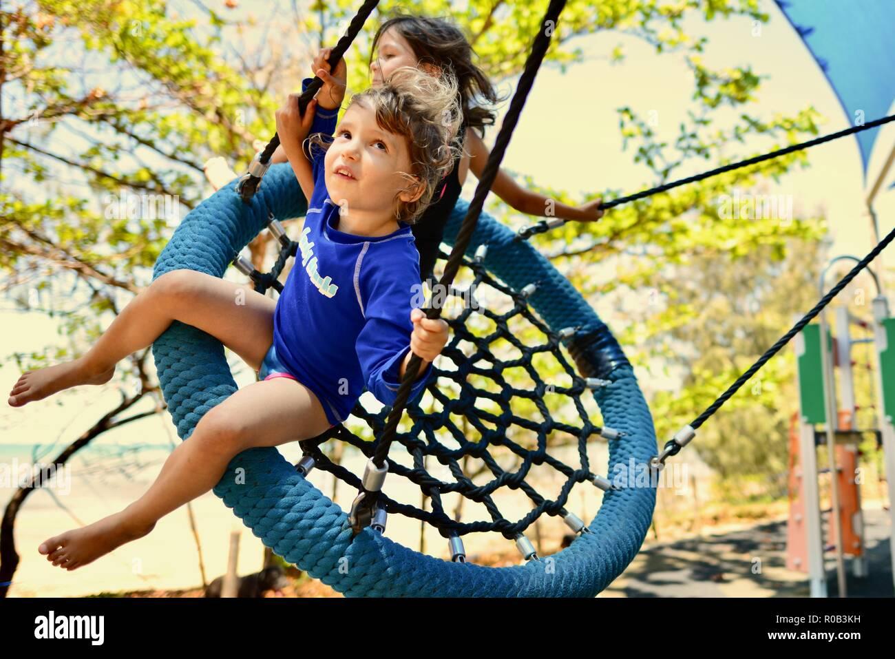 Two children playing on a nest swing, Balgal beach, QLD, Australia Stock Photo