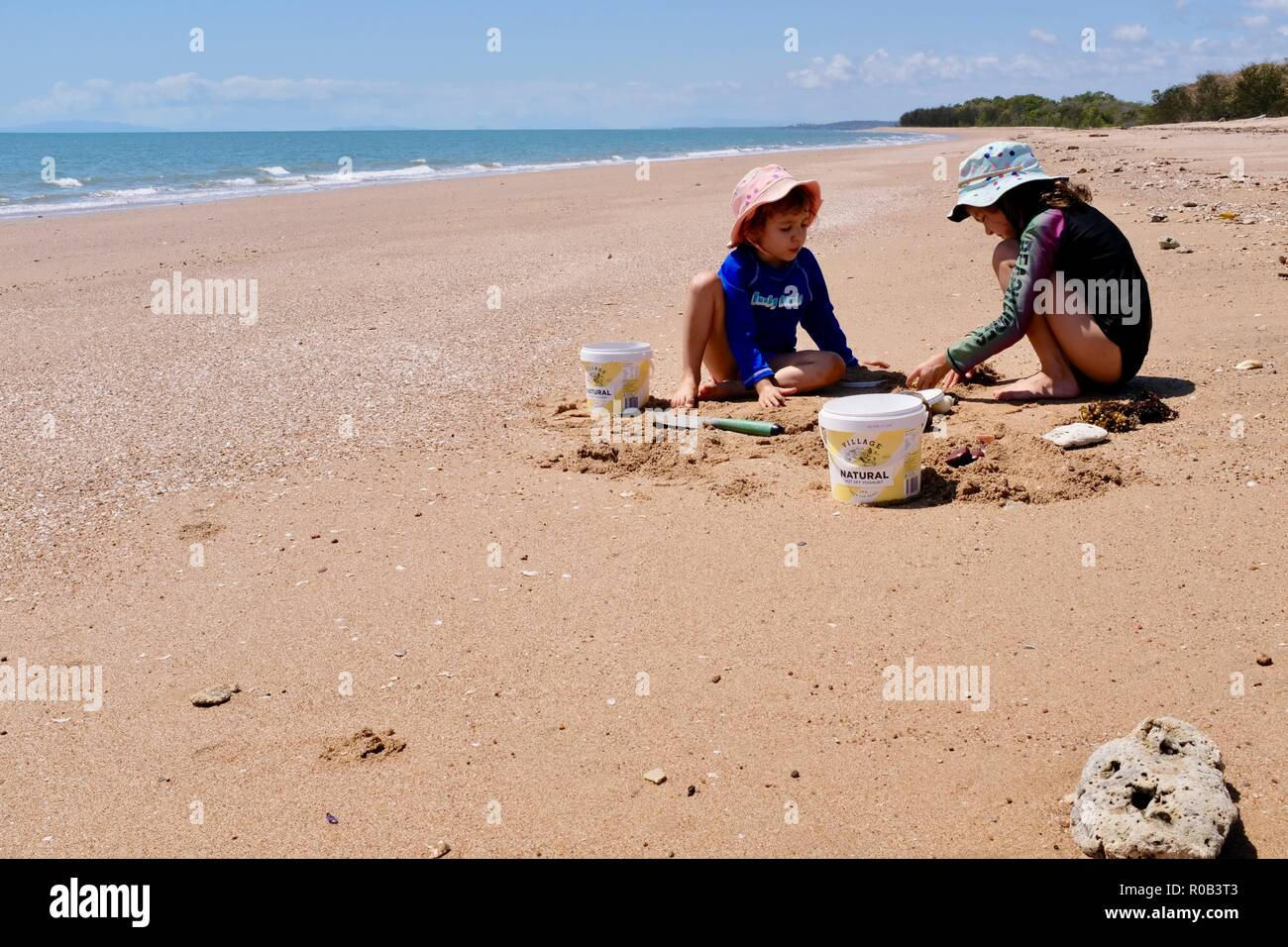 Children playing in the sand with buckets and spades, Balgal beach, QLD, Australia Stock Photo