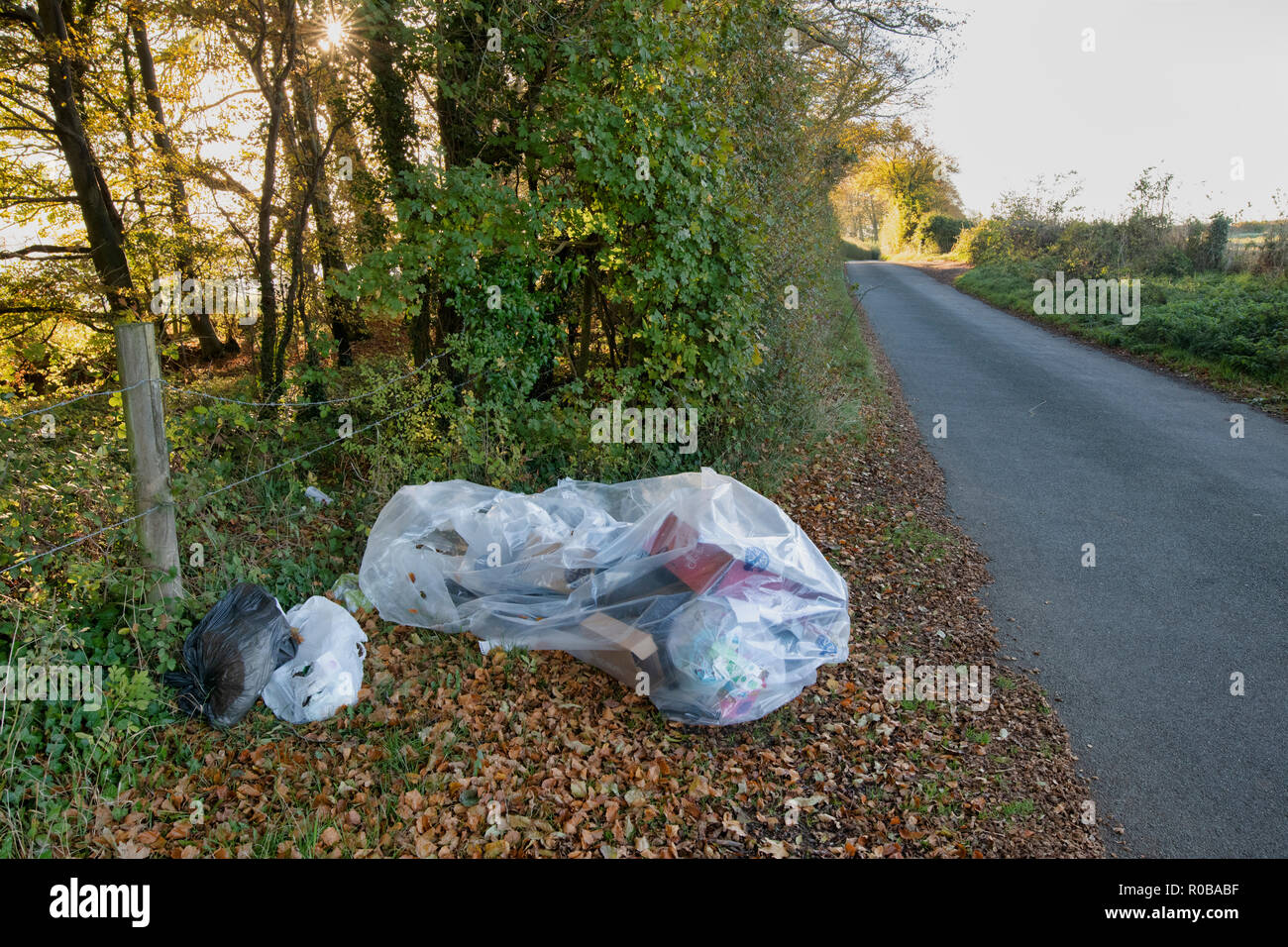 Fly tipped plastic and cardboard rubbish on a country road in the Cotswolds. The Slaughters, Cotswolds, Gloucestershire, England Stock Photo