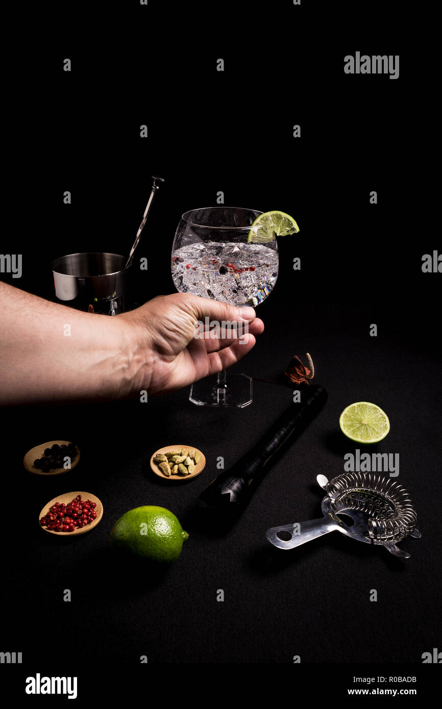 barman preparing a tasty and fresh gin and tonic cocktail on a black background next to his ingredients Stock Photo