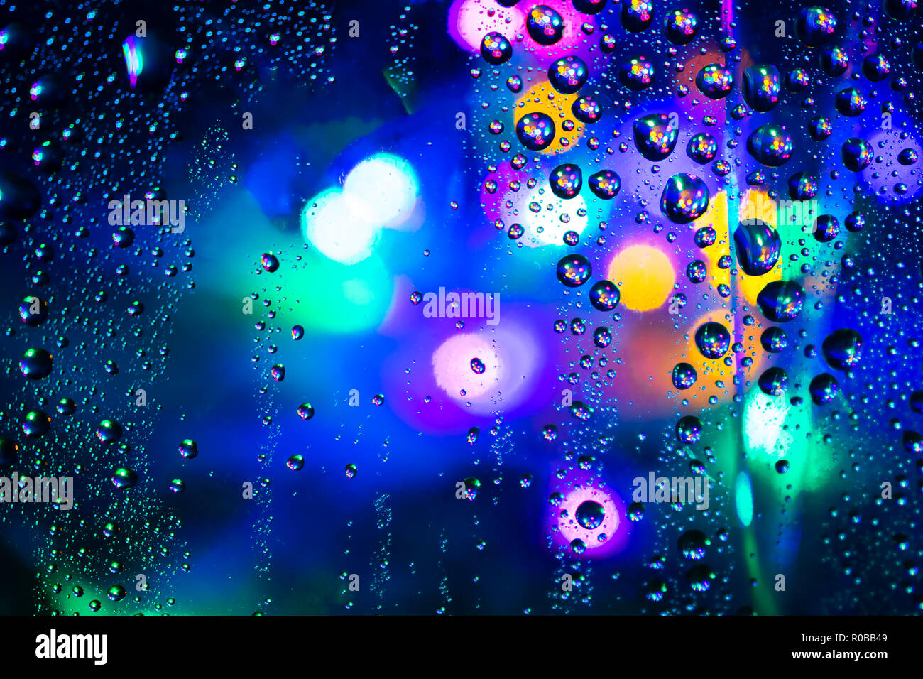 colored bokeh behind the splashes of water - Stock Image