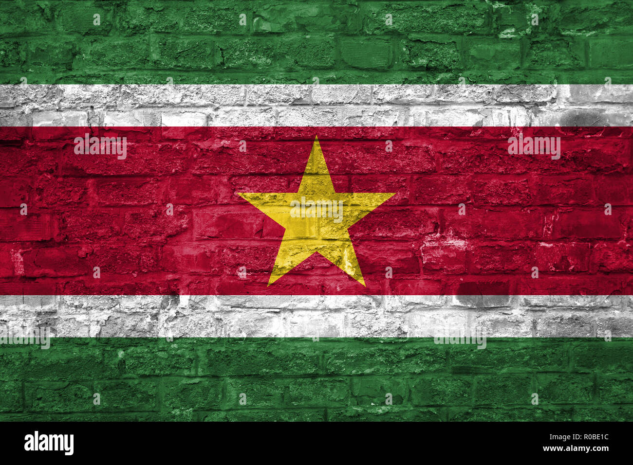 Flag of Suriname over an old brick wall background, surface - Stock Image