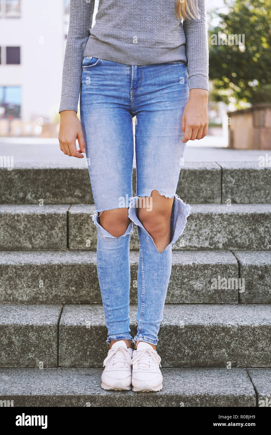 distressed denim fashion trend, ripped jeans with holes exposing knees of unrecognizable girl - Stock Image